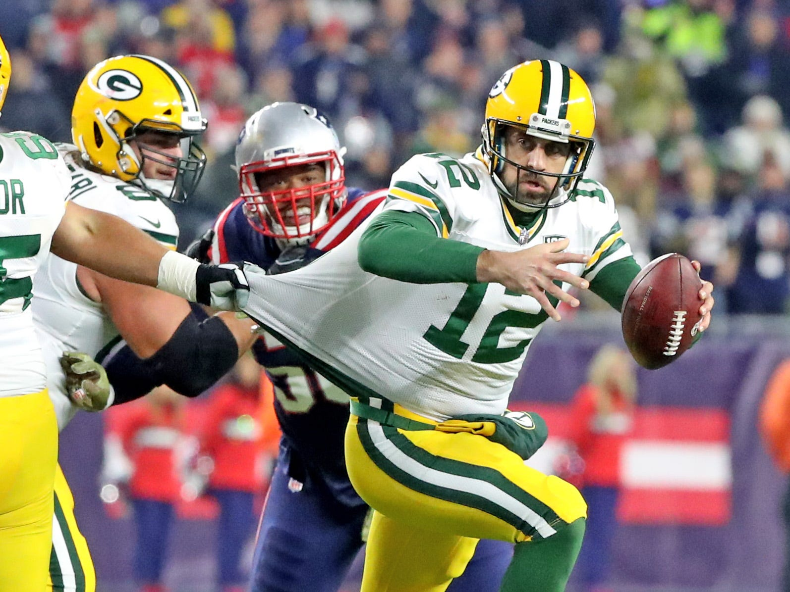 Green Bay Packers quarterback Aaron Rodgers (12) is grabbed by his jersey on a scramble against the New England Patriots Sunday, November 4, 2018 at Gillette Stadium in Foxborough, Mass.