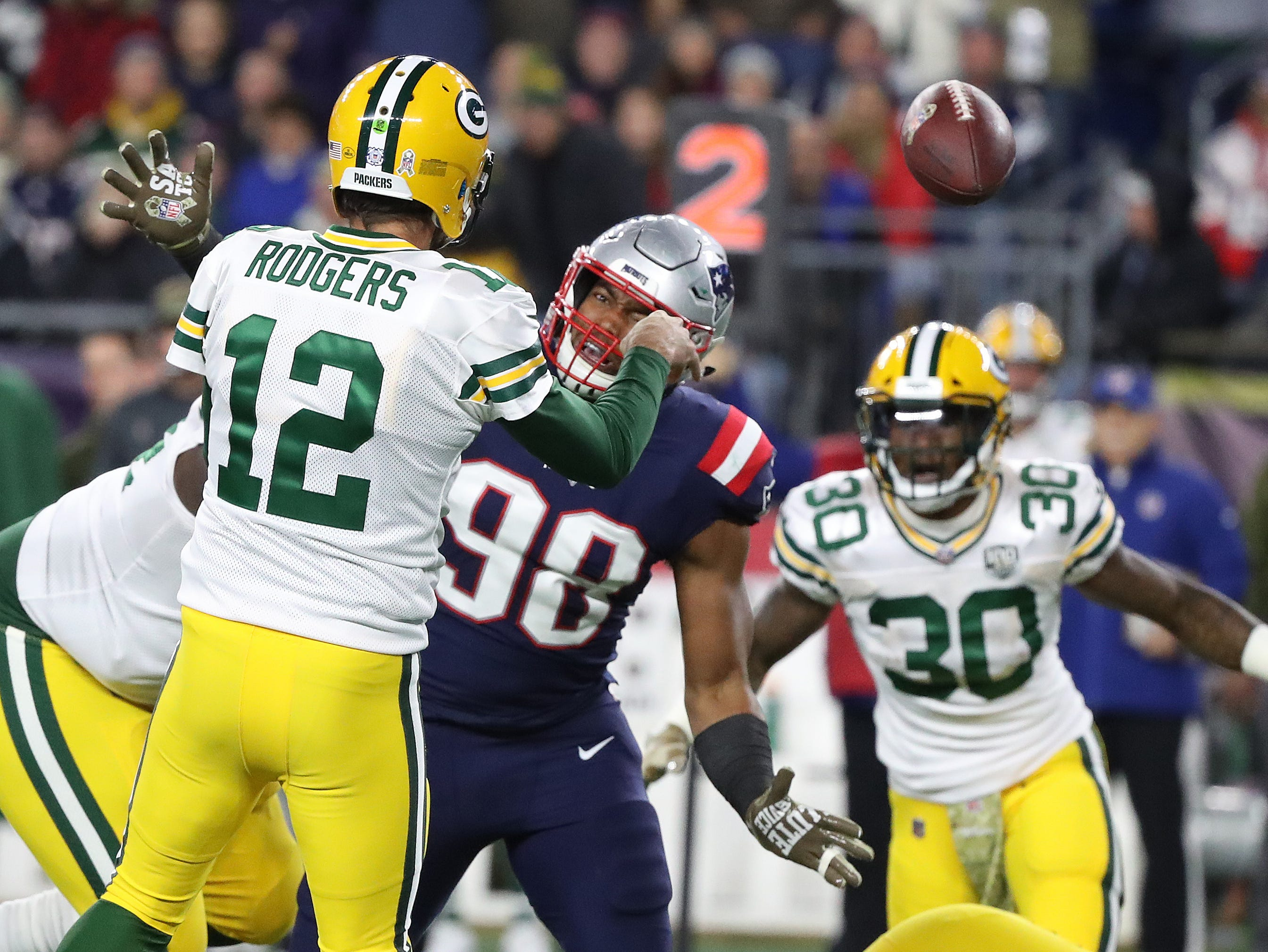 Green Bay Packers quarterback Aaron Rodgers (12) has two get rid of the ball as defensive tackle Malcom Brown (90) breaks into the pocket against the New England Patriots Sunday, November 4, 2018 at Gillette Stadium in Foxboro, Mass.