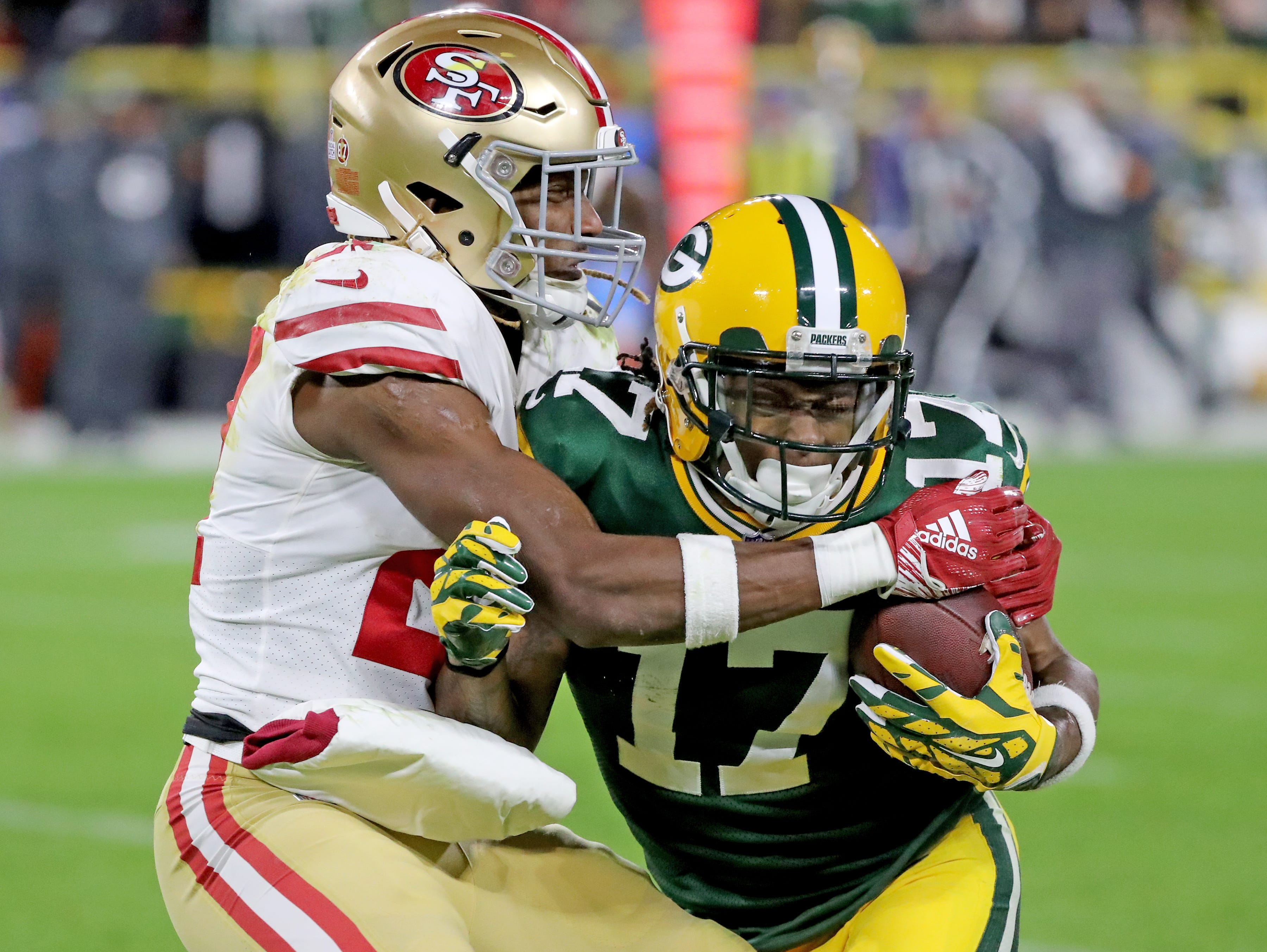 Green Bay Packers wide receiver Davante Adams (17) collides with free safety Adrian Colbert (27) against the San Francisco 49ers at Lambeau Field Monday, October 15, 2018 in Green Bay, Wis.