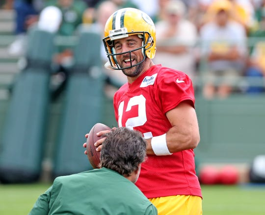 Green Bay Packers quarterback Aaron Rodgers (12) laughs as he takes a handoff during Green Bay Packers Training Camp Friday, July 27, 2018 at Ray Nitschke Field in Ashwaubenon, Wis
