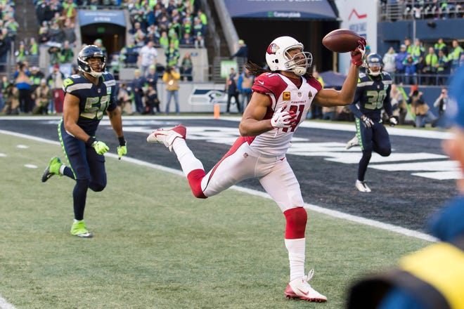 Dec 30, 2018: Arizona Cardinals wide receiver Larry Fitzgerald (11) catches a one-handed pass for a touchdown against the Seattle Seahawks during the first half at CenturyLink Field.