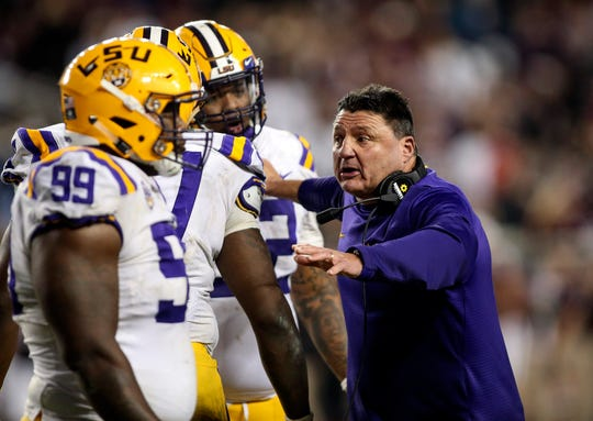 LSU coach Ed Orgeron talks with his players during the fifth overtime of a game against Texas A&M Aggies.