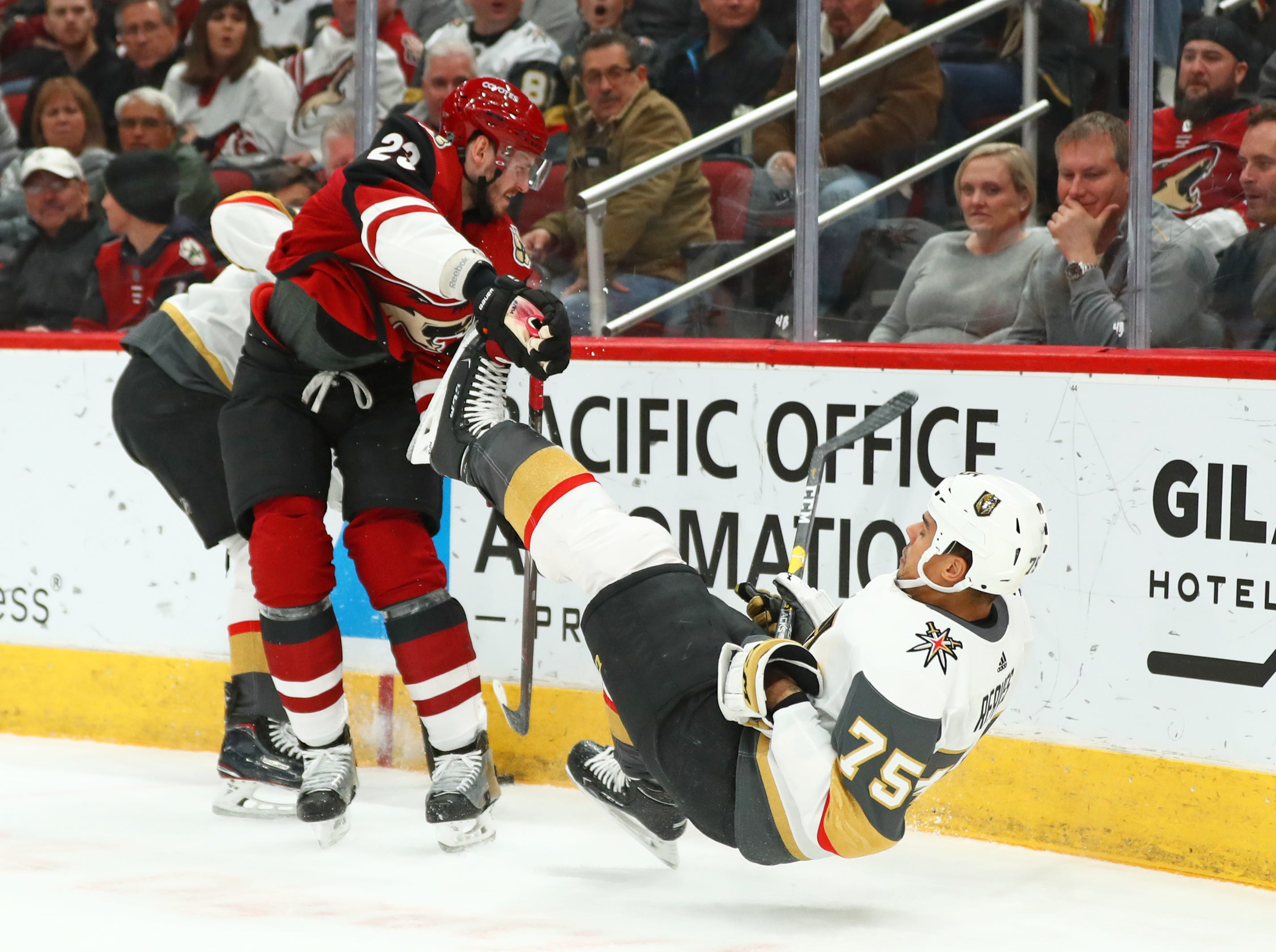 Dec 30, 2018; Glendale, AZ, USA; Vegas Golden Knights right wing Ryan Reaves (75) falls to the ice after being checked by Arizona Coyotes defenseman Oliver Ekman-Larsson (23) in the first period at Gila River Arena. Mandatory Credit: Mark J. Rebilas-USA TODAY Sports