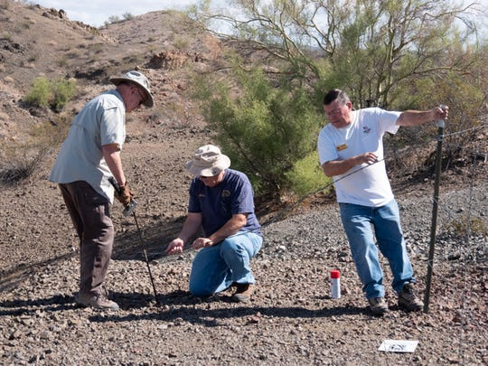 Havasu 4 Wheelers Club member Darryld Kautzmann holds a fence post steady while John Strong pushes a wire anchor down a steel rod, which Jim Bowen hammers into the dirt. They are repairing the fence around an abandoned mine where a club member almost fell to his death in 2008.