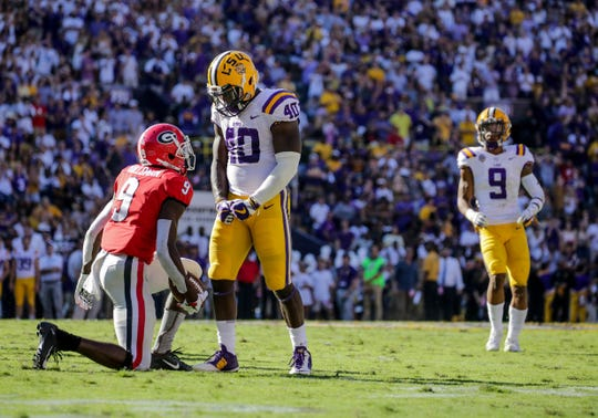 LSU linebacker Devin White (40) stands over Georgia receiver Jeremiah Holloman (9) and flexes during the second quarter of a game at Tiger Stadium.