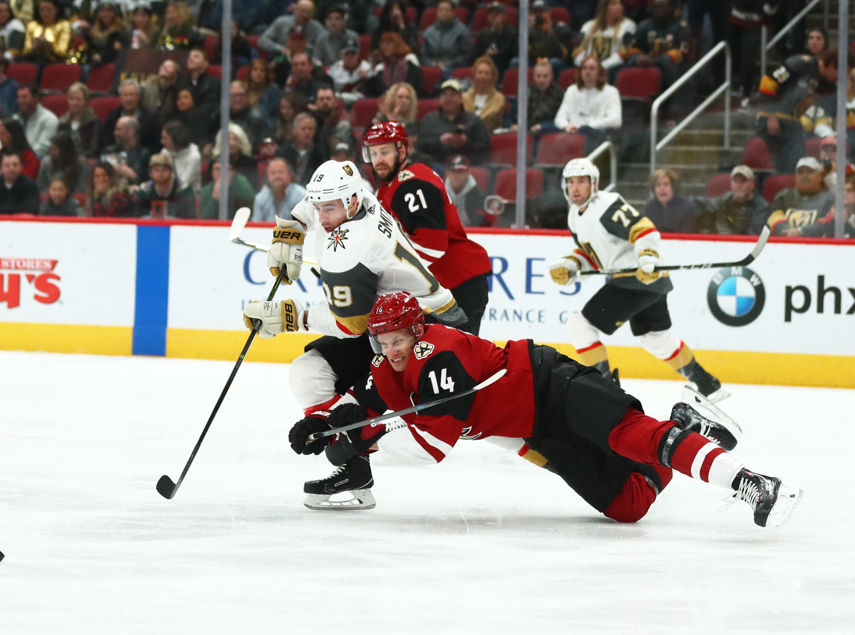 Dec 30, 2018; Glendale, AZ, USA; Arizona Coyotes right wing Richard Panik (14) falls to the ice as he battles for the puck against Vegas Golden Knights right wing Reilly Smith (19) in the first period at Gila River Arena. Mandatory Credit: Mark J. Rebilas-USA TODAY Sports