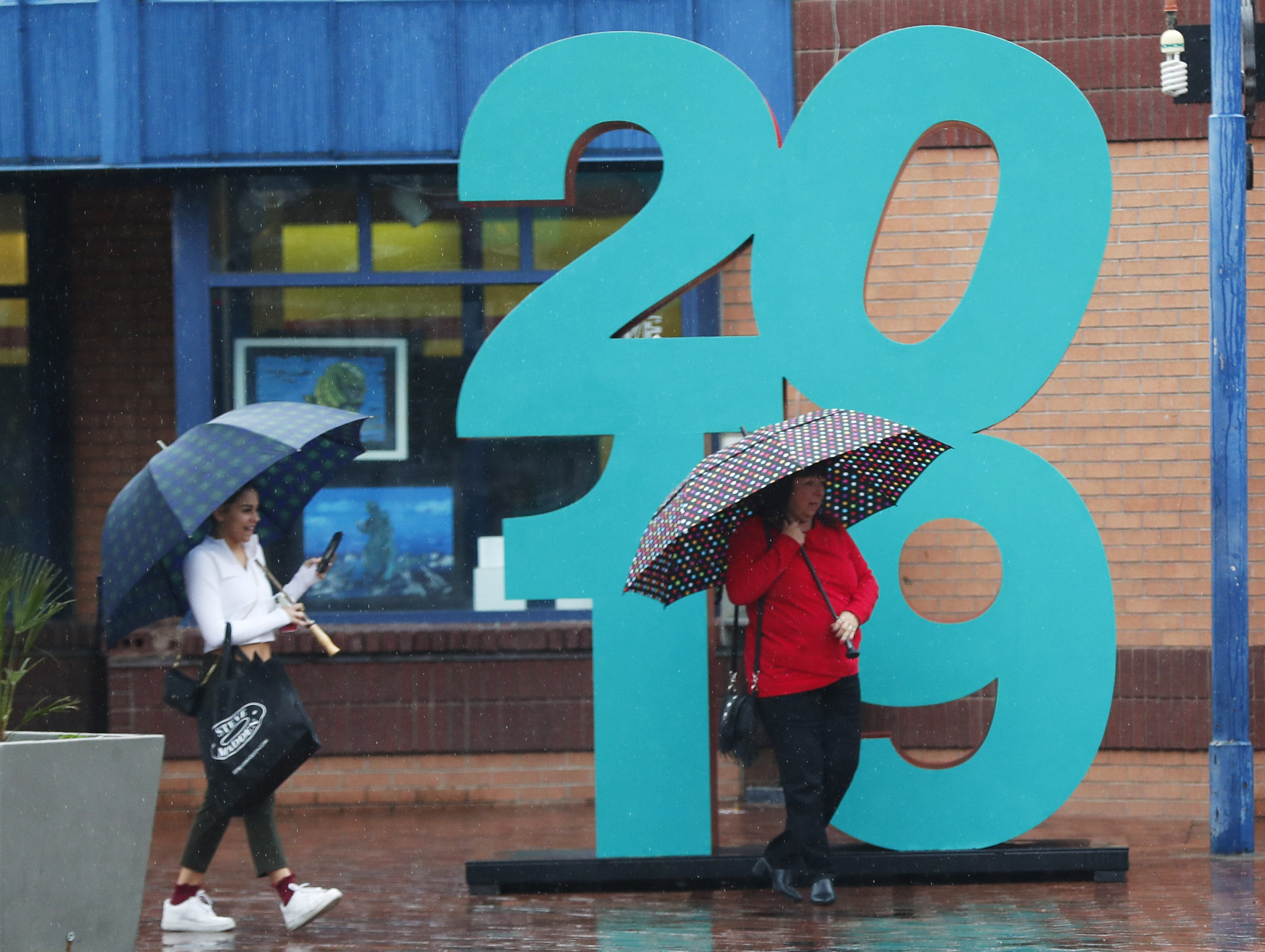 Pedestrians shield themselves from the rain near a 2019 sign in downtown Tempe on Dec. 31, 2018.