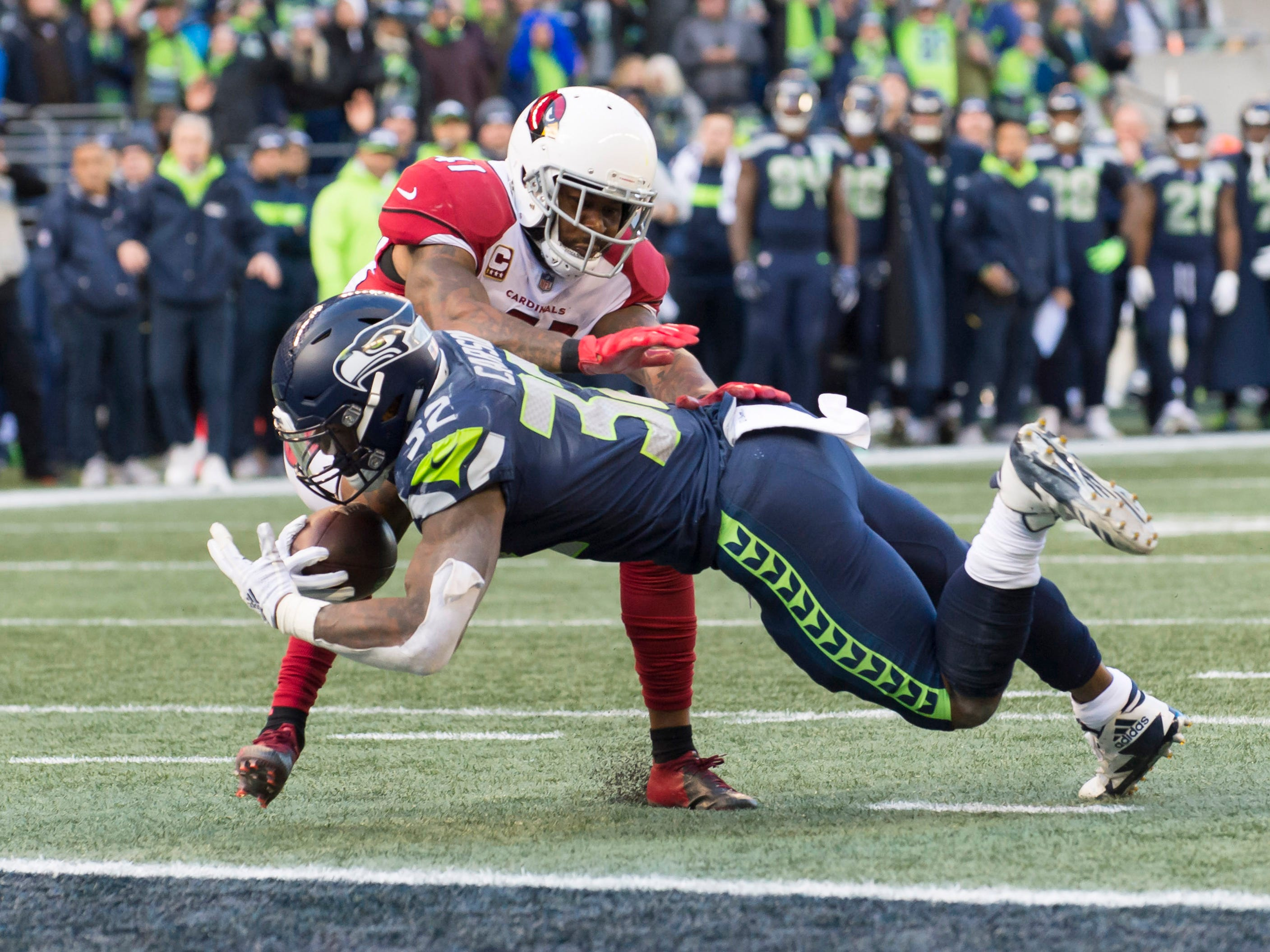 Dec 30, 2018; Seattle, WA, USA; Seattle Seahawks running back Chris Carson (32) carries the ball in for a touchdown during the first half against the Arizona Cardinals at CenturyLink Field. Mandatory Credit: Steven Bisig-USA TODAY Sports