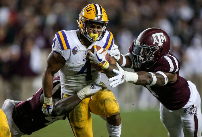 LSU running back Nick Brossette tries to break a tackle from Texas A&M linebacker Buddy Johnson during the fifth overtime of a game at Kyle Field.