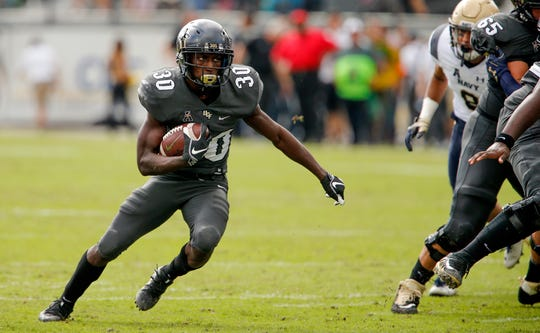 UCF running back Greg McCrae carries the ball during the first quarter of a game against Navy.