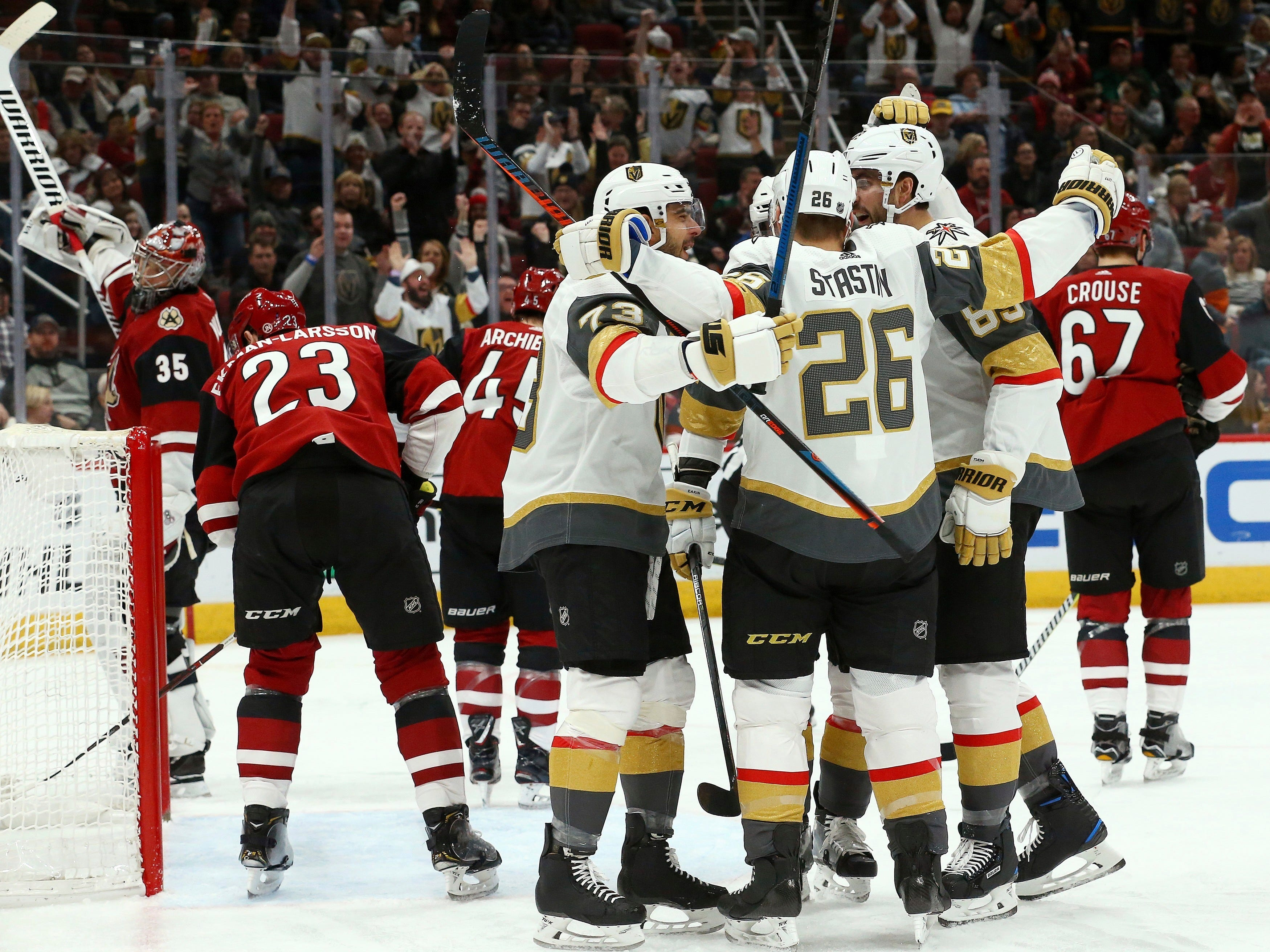 Vegas Golden Knights center Paul Stastny (26) celebrates his goal against the Arizona Coyotes with left wing Valentin Zykov (73) and right wing Alex Tuch (89) as Coyotes goaltender Darcy Kuemper (35) and Coyotes defenseman Oliver Ekman-Larsson (23) look for the puck during the first period of an NHL hockey game Sunday, Dec. 30, 2018, in Glendale, Ariz. (AP Photo/Ross D. Franklin)