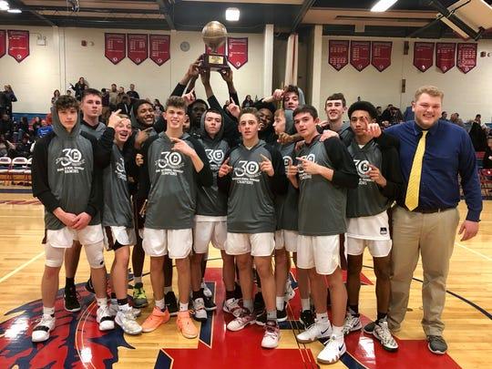 The Arlington High School boys basketball team poses after winning the Duane Davis Memorial tournament final on Sunday.