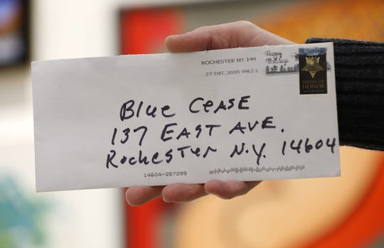 "Bleu Cease holds the hate mail envelope, addressed to him with an incorrect spelling of his first name. Cease took the ""cool, artsy and with it"" quote from the letter and put it on a T-shirt to raise money for the Rochester Contemporary Art Center."