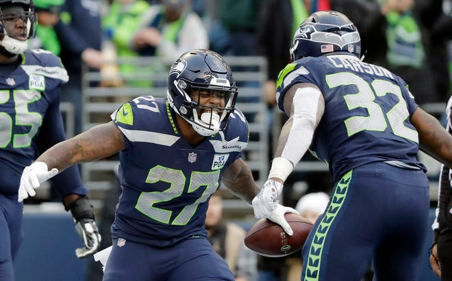 Seattle Seahawks' Mike Davis (27) celebrates his touchdown with Chris Carson during the second half of an NFL football game against the Arizona Cardinals, Sunday, Dec. 30, 2018, in Seattle.
