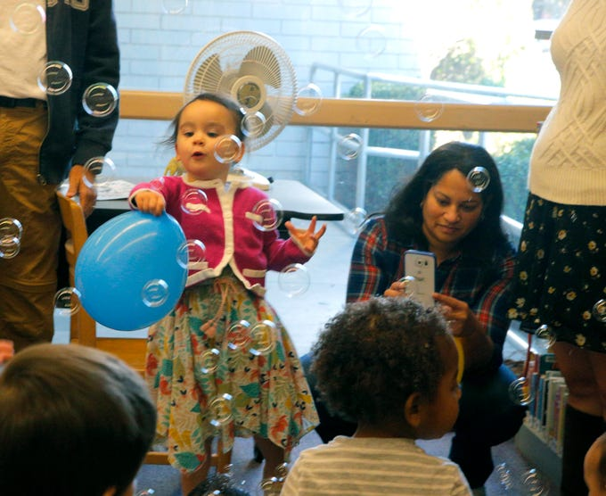 Rosemary Irvine, 2, plays with a balloon and bubbles Monday at the John Steinbeck Library's New Year's Eve celebration.