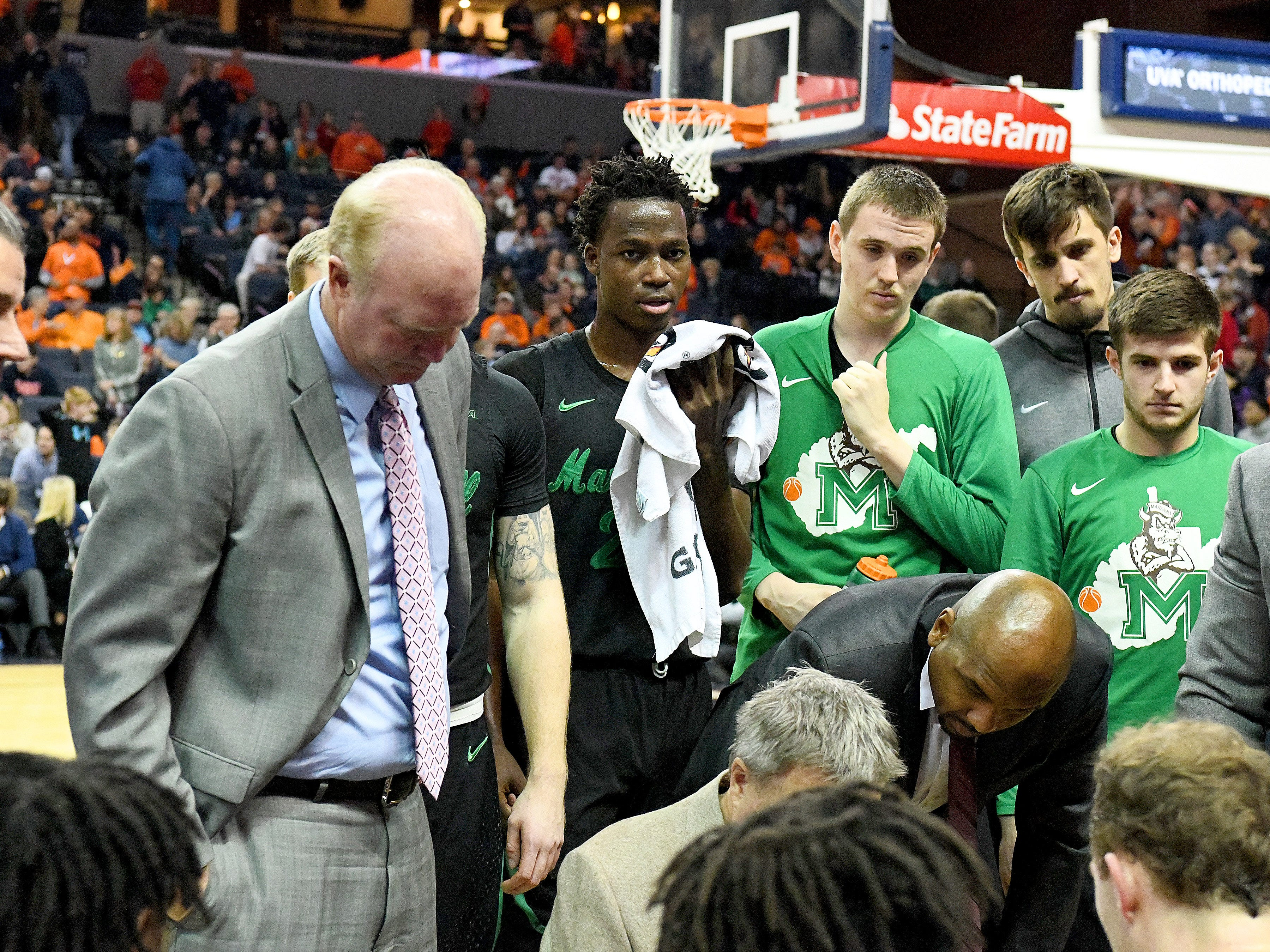 Marshall's Darius George, former R.E. Lee star, listens to the coach who speaks to the team in a timeout during their game against University of Virginia, played at the John Paul Jones Arena on Dec. 31, 2016.