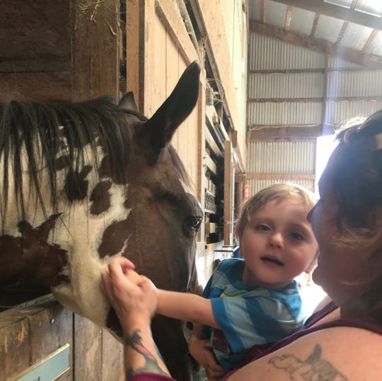 Kelly Howe, of Staunton, holds her 3-year-old grandson Carson Tugman, so he can pet horses at Cedar Creek Stables during Ride with Pride. Tugman suffers from a progressive neurodevelopmental disorder caused by a pathogenic variant of the MECP2 gene known as Rett Syndrome.