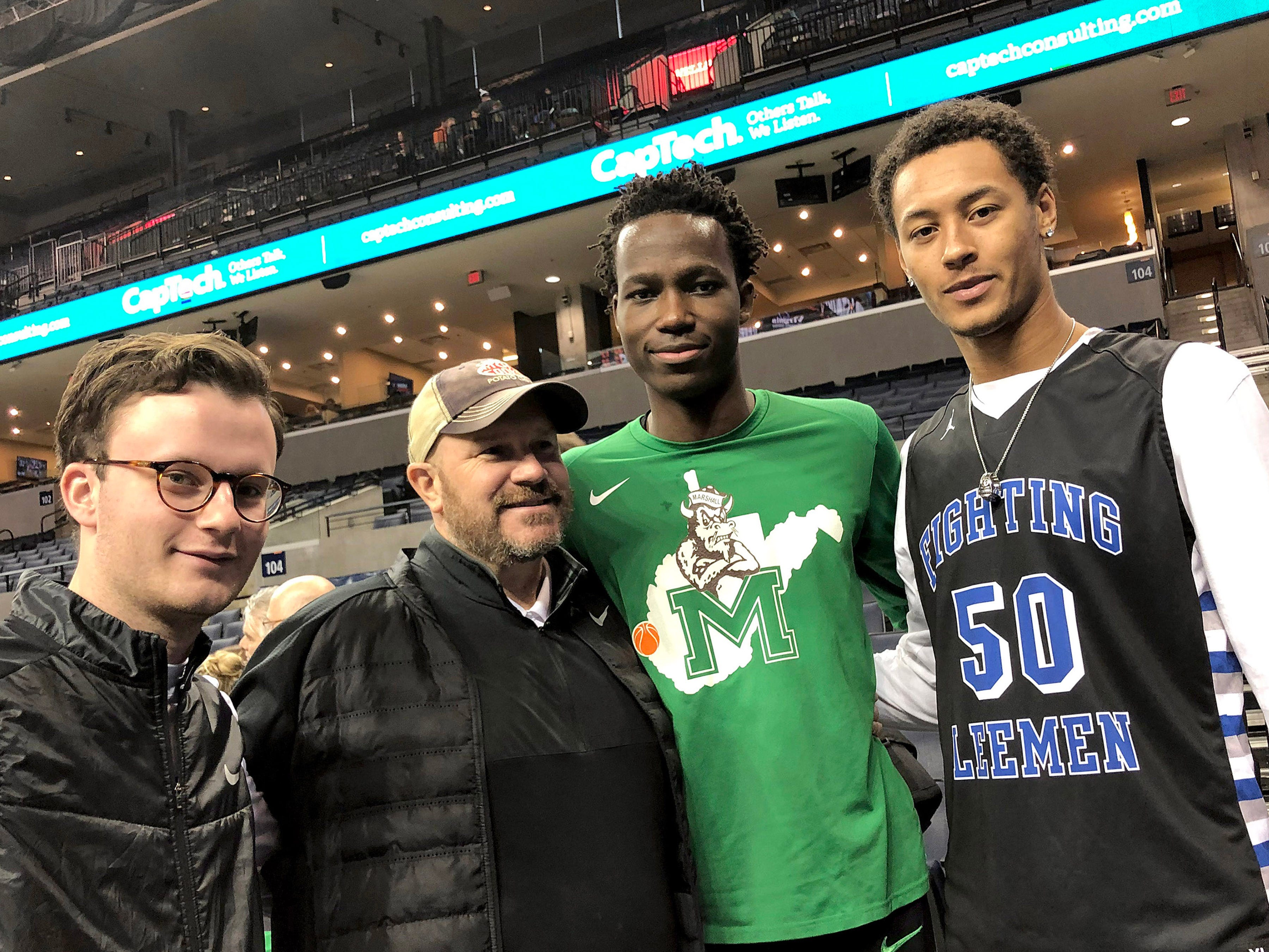 Marshall's Darius George (center), former R.E. Lee star, is photographed with his high school coach, Jarrett Hatcher as well as R.E. Lee former assistant coach Sam LaClair (far left) and former teammate Jarvis Vaughan (far right) after Marshall's game against the University of Virginia, played at the John Paul Jones Arena on Dec. 31, 2016.