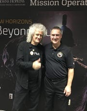 """Mark Lahr stands with NASA fan and lead guitarist of """"Queen"""" Brian May on his visit for New Horizons' historic mission."""