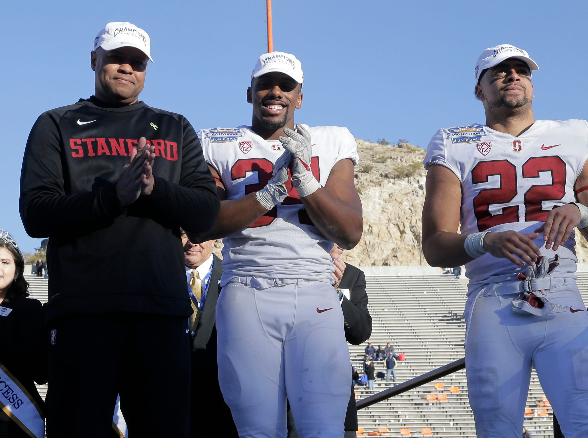 Head coach David Shaw and Thomas Booker and Cameron Scarlett both members of the Stanford football team wait for the presentation of the 85th Hyundai Sun Bowl Championship trophy after defeating the Pitt Panthers 14-13.