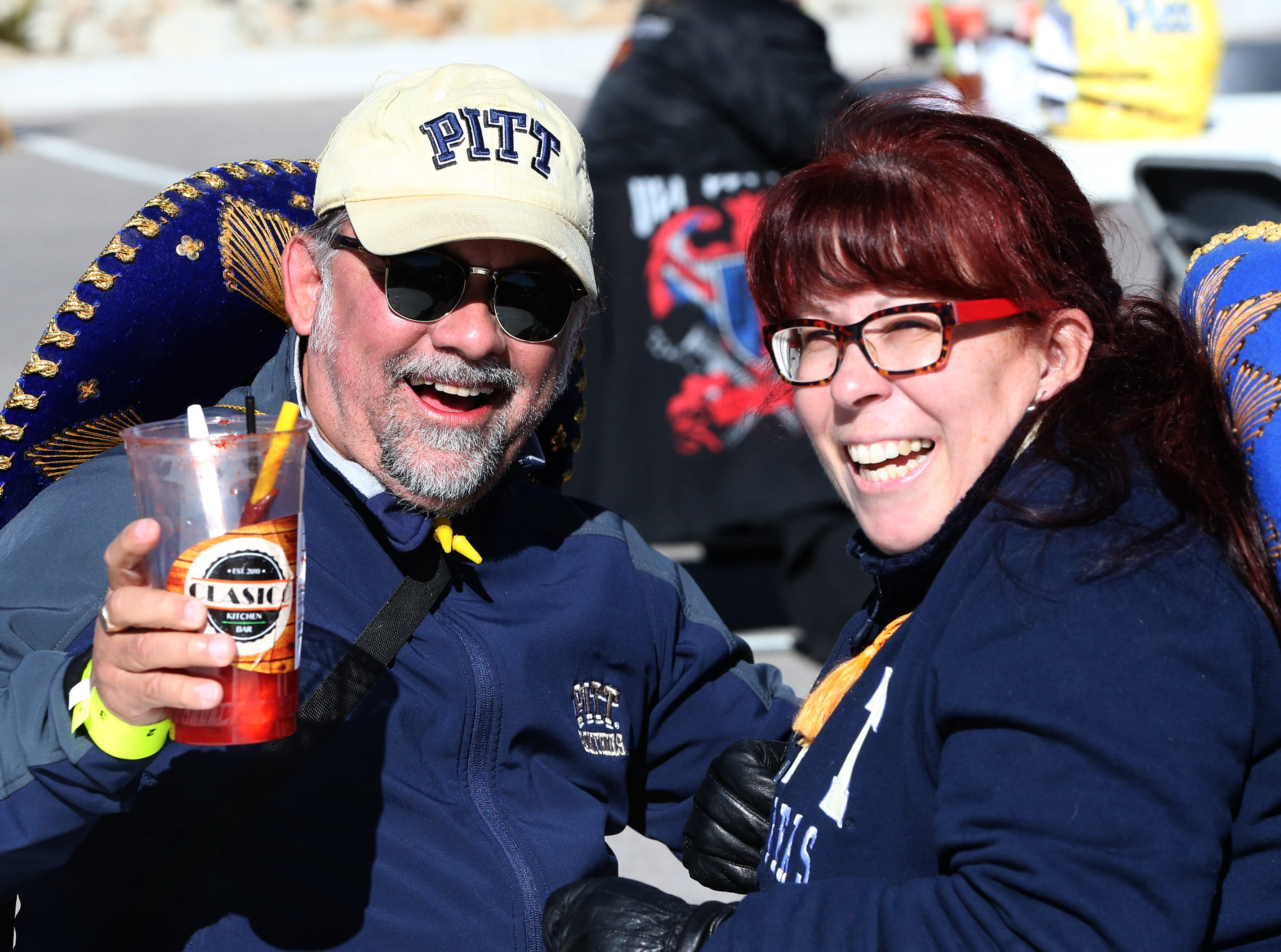 Rolando and Mimi Flores of Albuquerque enjoy drinks at a pre-game tailgate in the North end of the Sun Bowl Monday. Rolando is a Pitt alum.