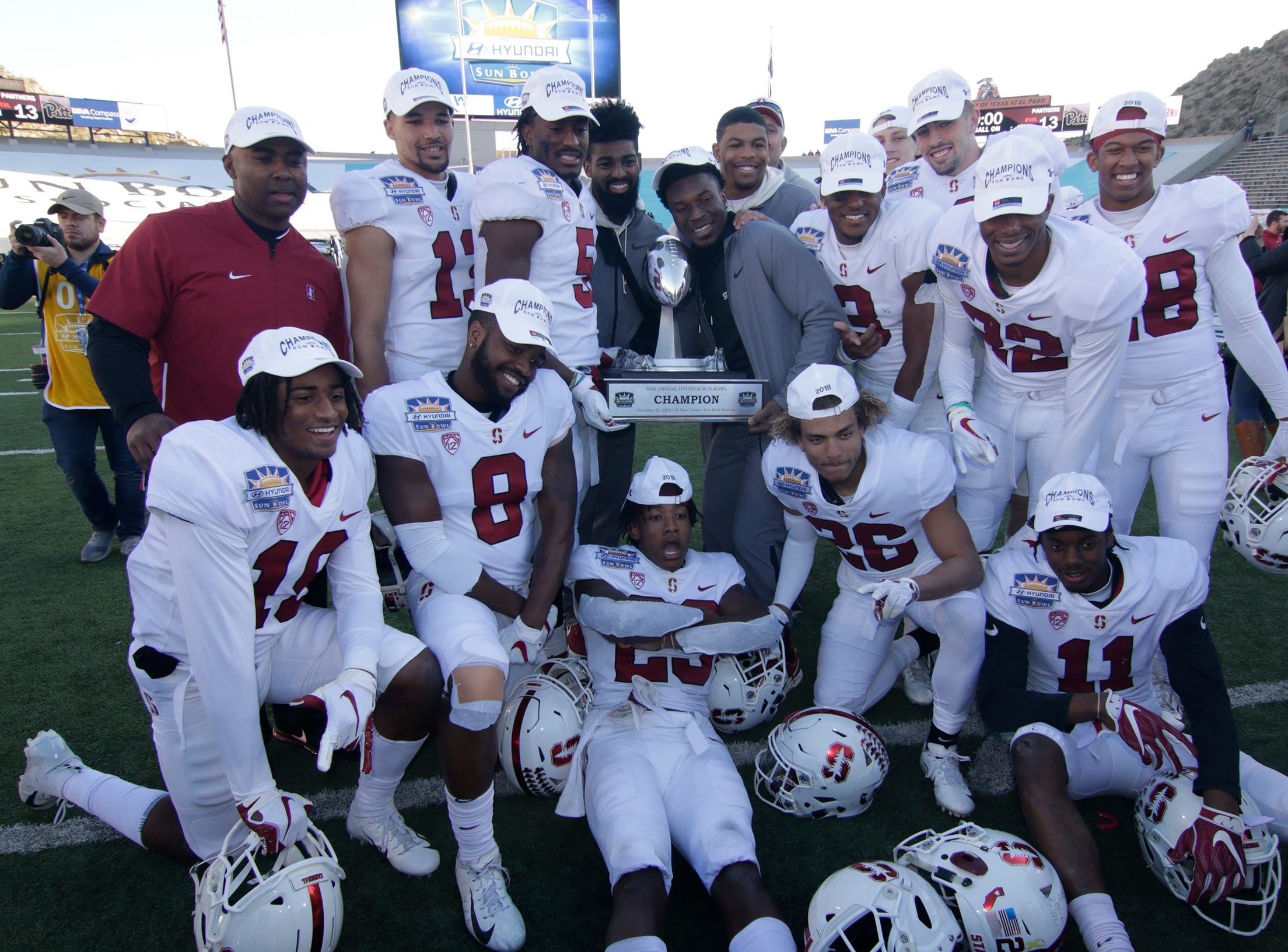 Members of the Stanford football team hold the 85th Hyundai Sun Bowl Championship trophy after defeating the Pitt Panthers 14-13.