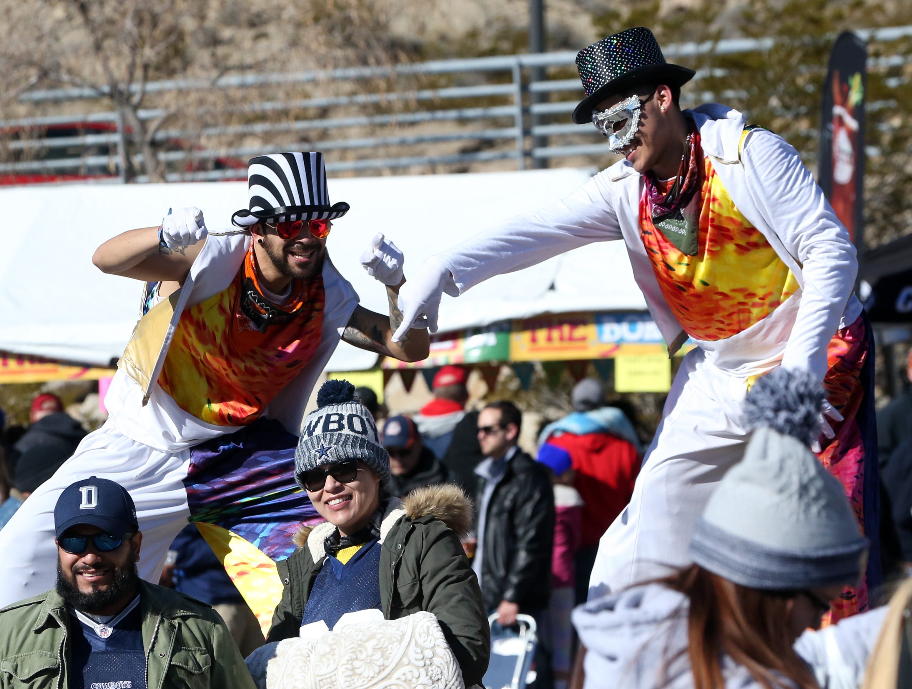 People on stilts greet fans at a pre-game party on the North end of the Sun Bowl Stadium Monday.