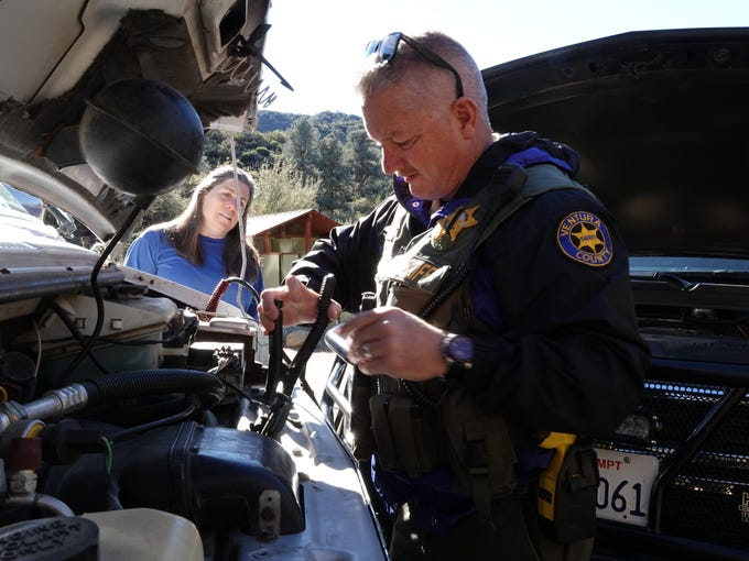 Deputy Bob Steele, of the Ventura County Sheriff's Office, jump-starts Dwylene Zapparelli's van at the Reyes Creek Campground on Dec. 29. Steele is one of two live-in deputies at the Lockwood Valley substation responsible for patrolling 610 square miles of remote terrain.