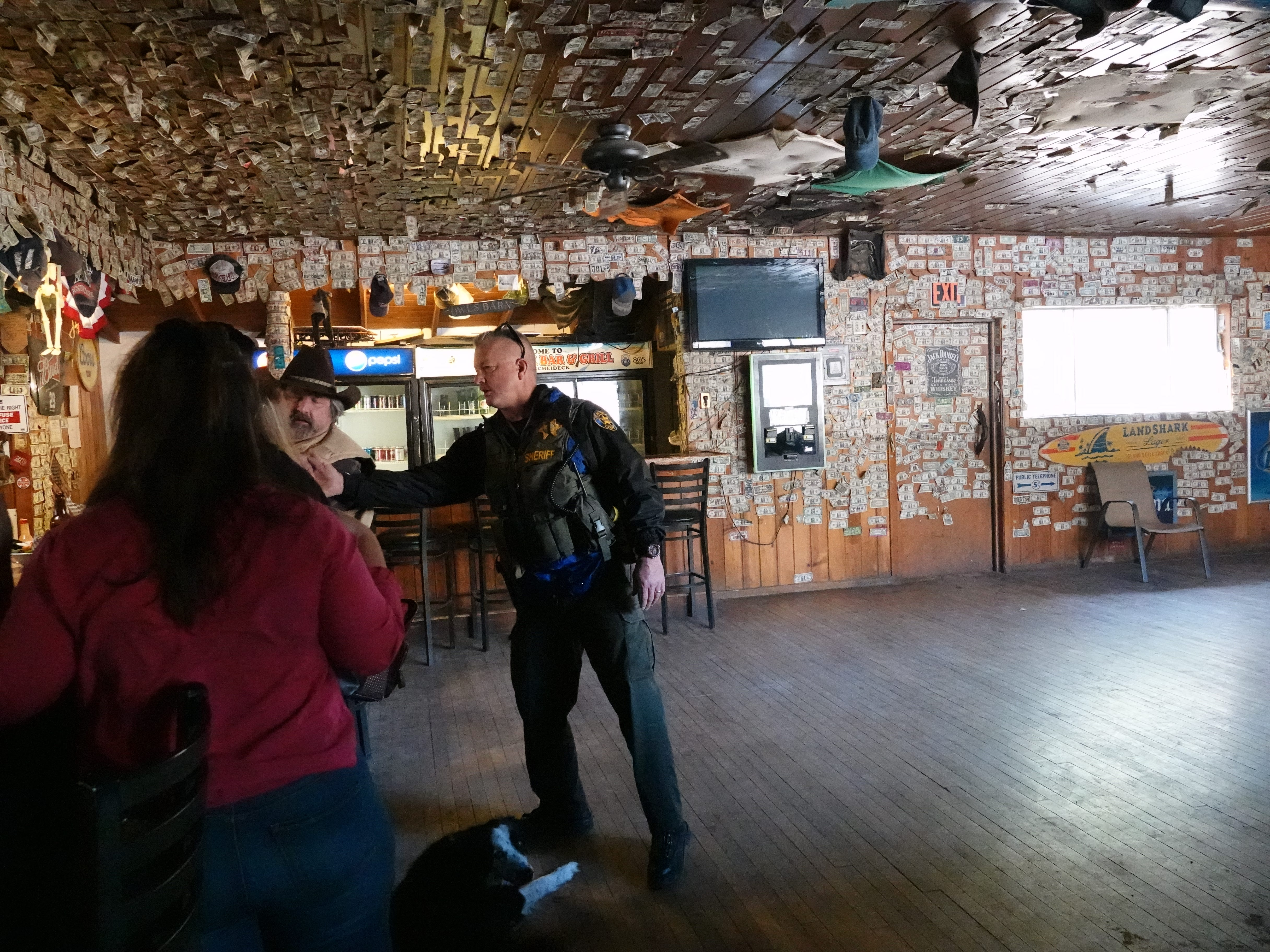 Ventura County Deputy Bob Steele leans over to shake a patron's hand inside the Reyes Creek Bar and Grill. Steele is one of two deputies who patrol 610 square miles of rugged terrain from the remote Lockwood Valley substation.