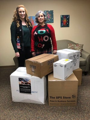 Aria Asselta (left), marketing coordinator for Eye Associates and the SurgiCenter of Vineland, with Lydia Pratts, an employee of Eye Associates and the SurgiCenter of Vineland, are pictured with boxes of donations, which will be sent to Kuwait for Pratts' son's military troop.