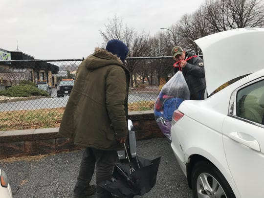 Volunteer Mark Puican helps Royce Brown and his girlfriend load their belongings to take to the motel where they will stay temporarily.