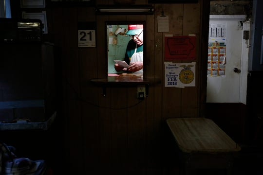 Owner Bob Hayes looks at orders at Holy Cross Meat Locker in Holy Cross, Iowa.