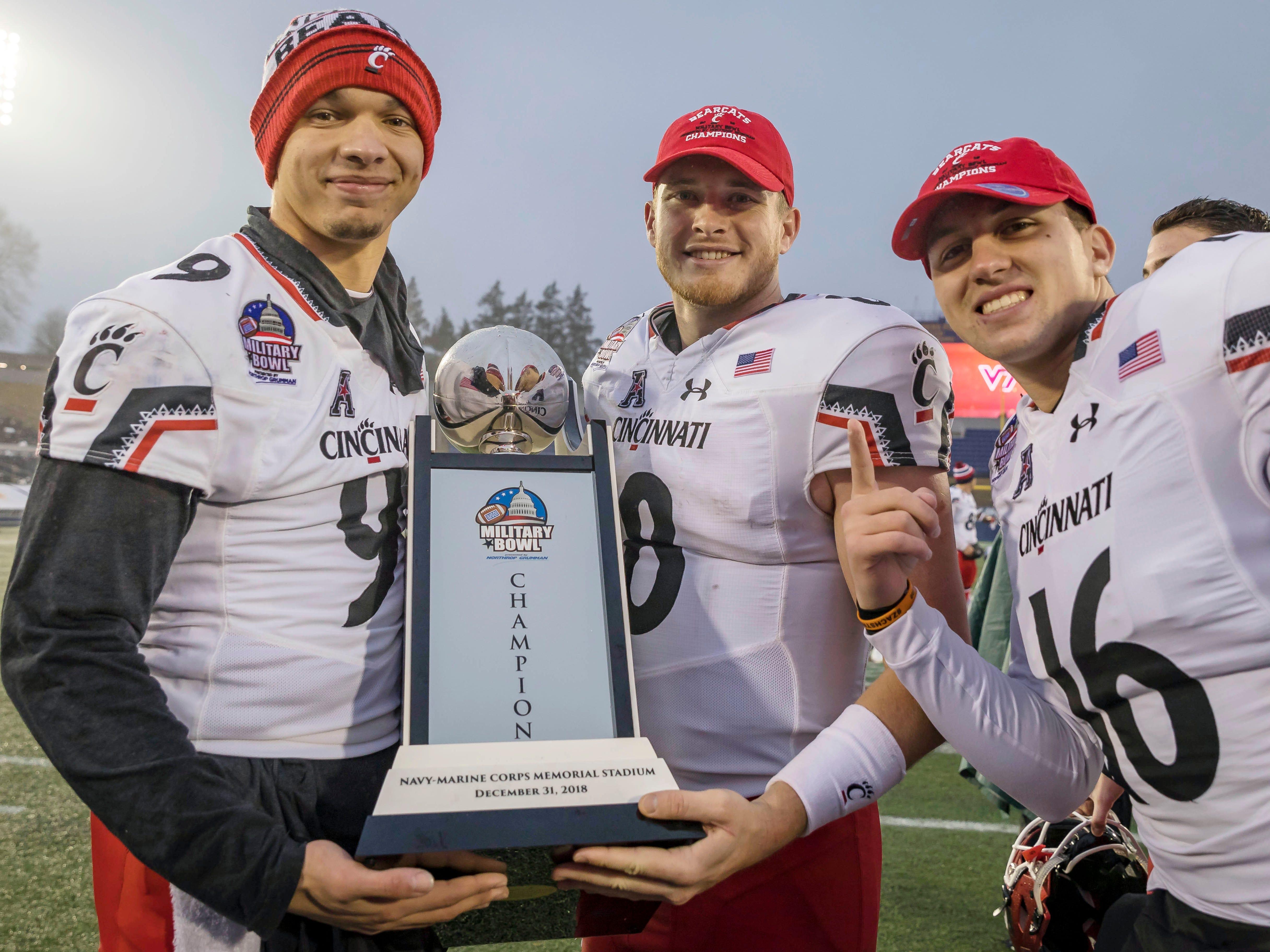 Cincinnati quarterbacks Desmond Ridder (9), Hayden Moore (8) and quarterback John Keller pose with the 2018 Military Bowl trophy after beating Virginia Tech.