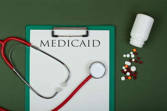 "Doctor workplace - red stethoscope, pills, medical bottle and clipboard with text ""medicaid"" on green paper background"