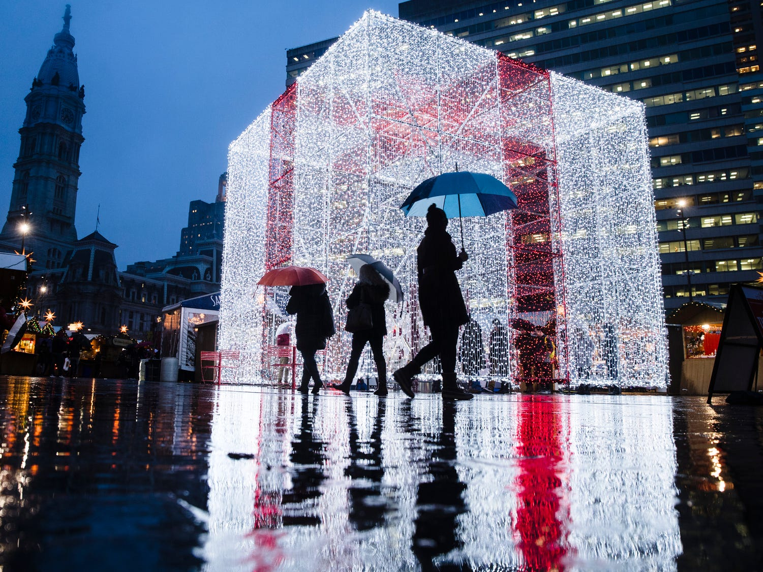 People walk on a rainy evening by The Present in the Christmas Village at John F. Kennedy Plaza, commonly known as Love Park, in Philadelphia, Dec. 20, 2018.