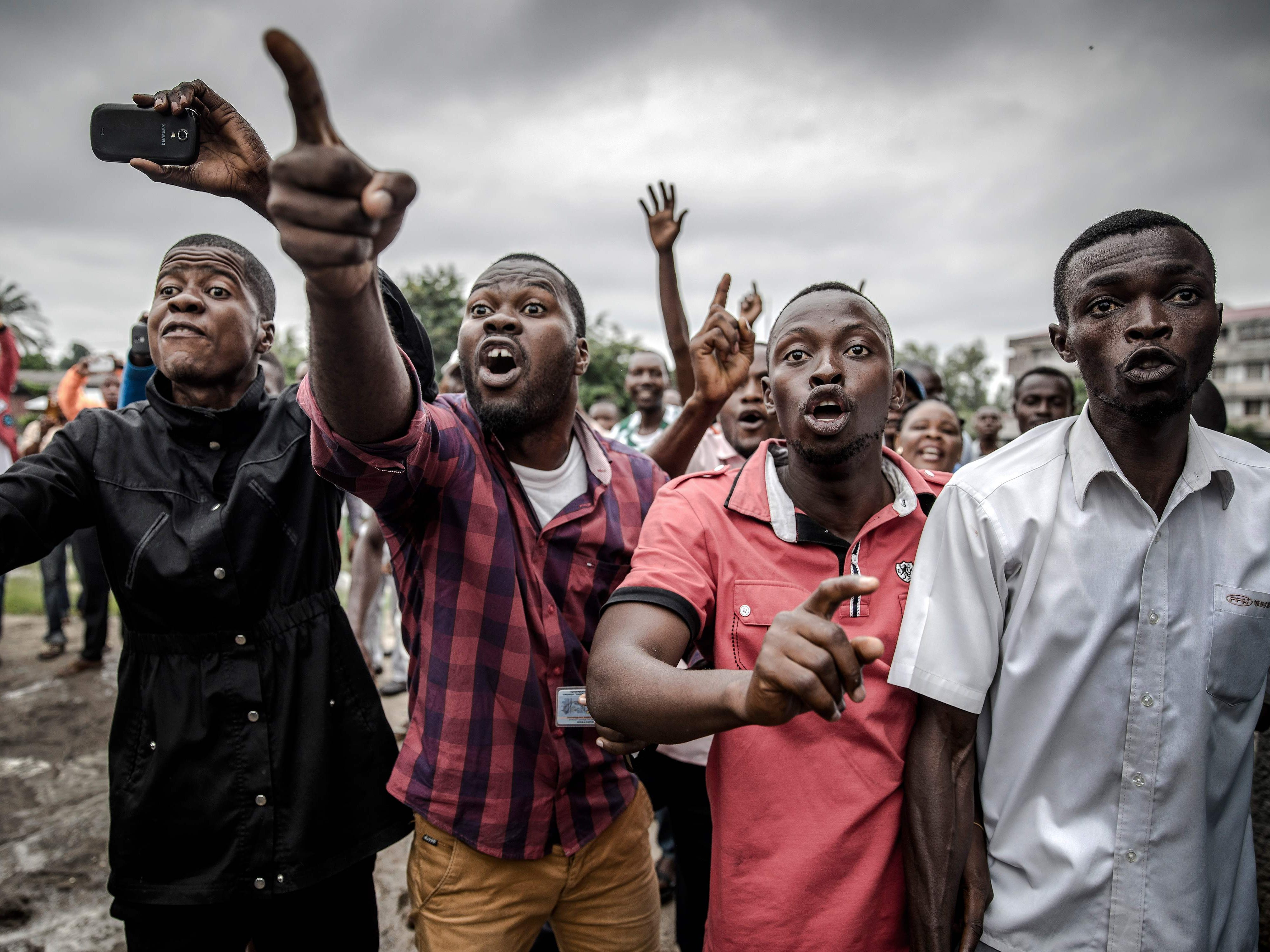 Protesters waiting to cast their ballot, demonstrate outside the College St Raphael polling station, in Kinshasa, on Dec. 30, 2018 while DRC's electoral commission president arrives for the DR Congo's general elections. Voters in the Democratic Republic of Congo went to the polls on Dec. 30, 2018 in elections that will shape the future of their vast, troubled country, amid fears that violence could overshadow the ballot.