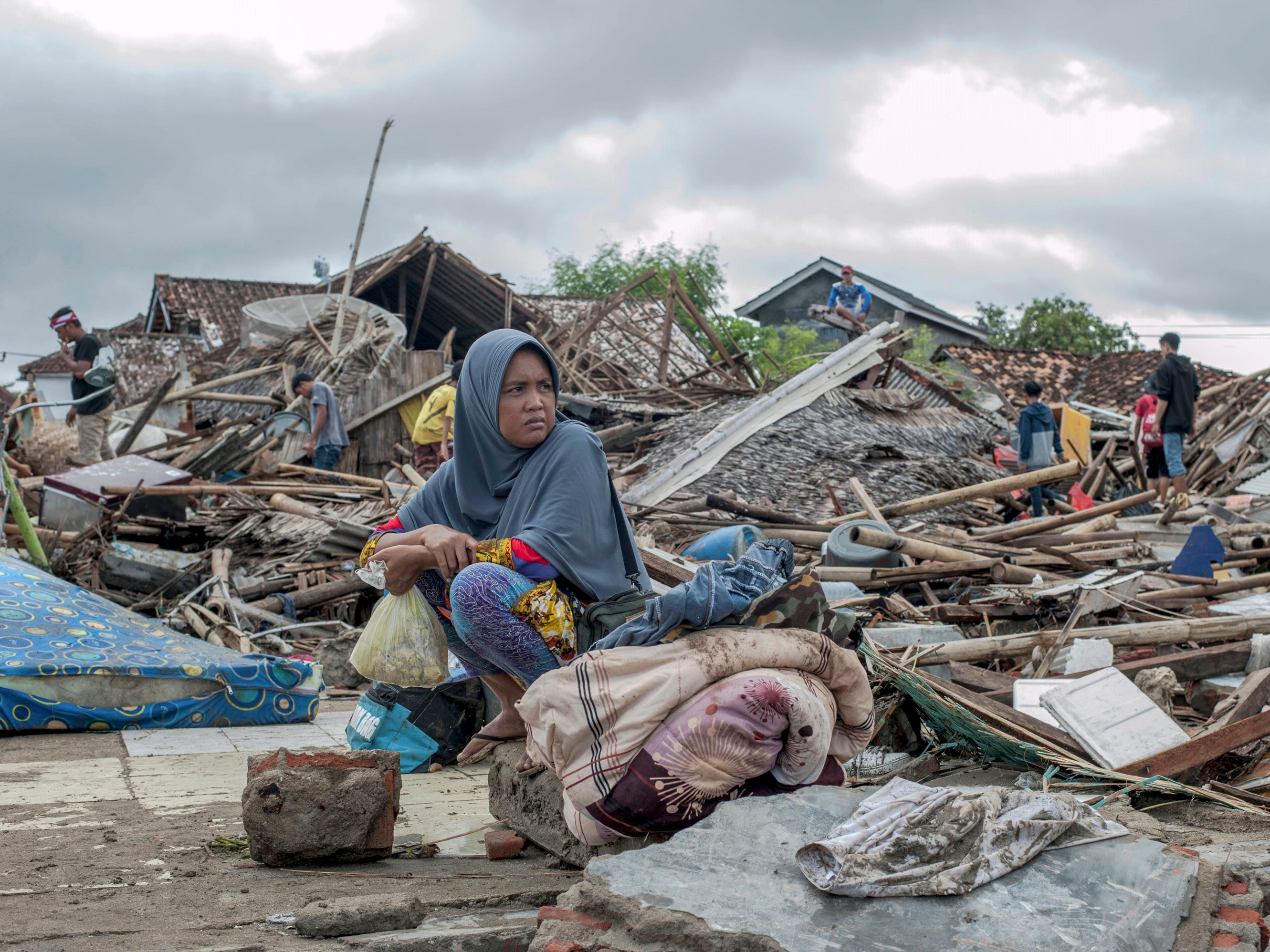 A tsunami survivor sits on a piece of debris as she salvages items from the location of her house in Sumur, Indonesia, Dec. 24, 2018. Doctors worked to save injured victims while members of the military and volunteers scoured debris-strewn beaches in search of survivors after a deadly tsunami gushed ashore without warning on Indonesian islands on a busy holiday weekend.