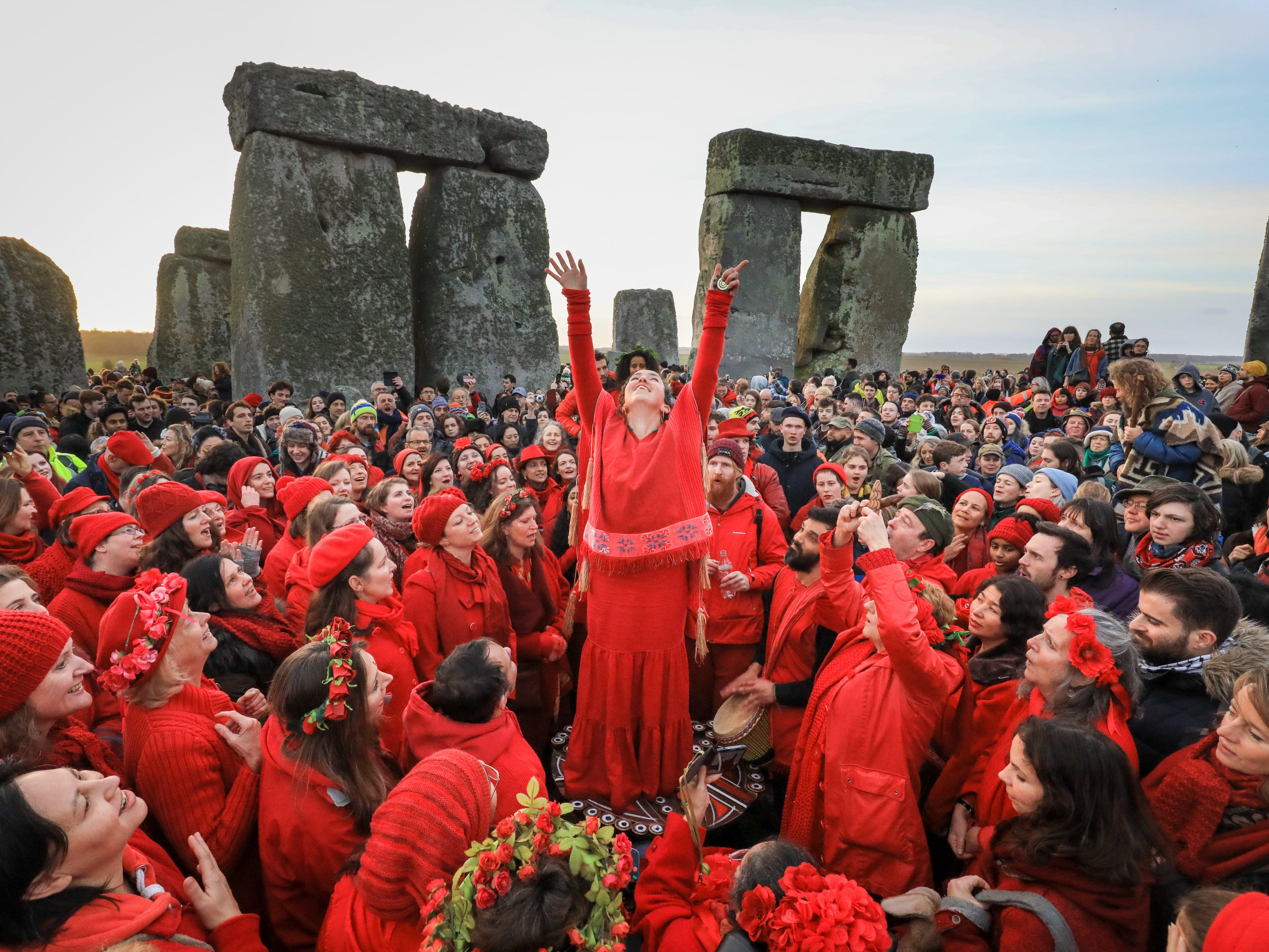 Members of the Shakti Sings choir sing as druids, pagans and revellers gather in the center of Stonehenge, hoping to see the sun rise, as they take part in a winter solstice ceremony at the ancient neolithic monument near Amesbury on Dec. 22, 2018 in Wiltshire, England.