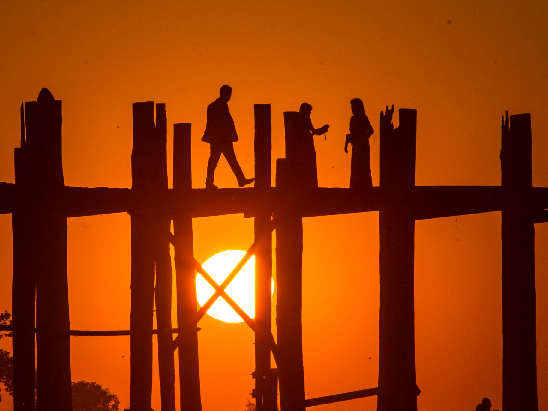 The last sunset of the year is seen over the U Paing (U Bein) Bridge at Taungthaman lake in Mandalay, Myanmar. The footbridge stretches over Taungthaman Lake connecting its two banks near Amarapura. Built by village mayor U Paing around 1850, it is considered the longest teakwood bridge in the world.