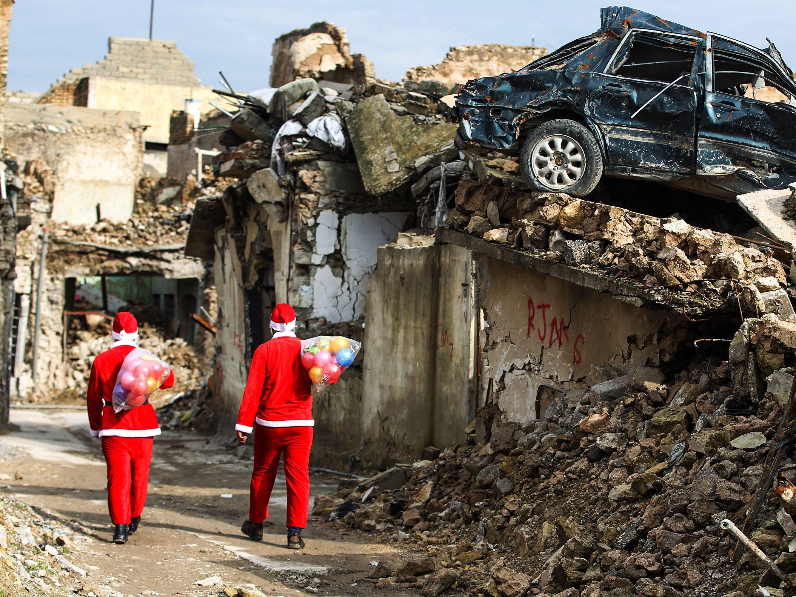 Iraqi youths dressed in Father Christmas suits walk through the streets of the old city of Mosul as they distribute gifts, on Dec. 26, 2018.  Iraq on Dec. 10 marked the first anniversary since declaring victory in its three-year war against the Islamic State (IS) group, which had left the country's former second city and the jihadists' capital in ruin.