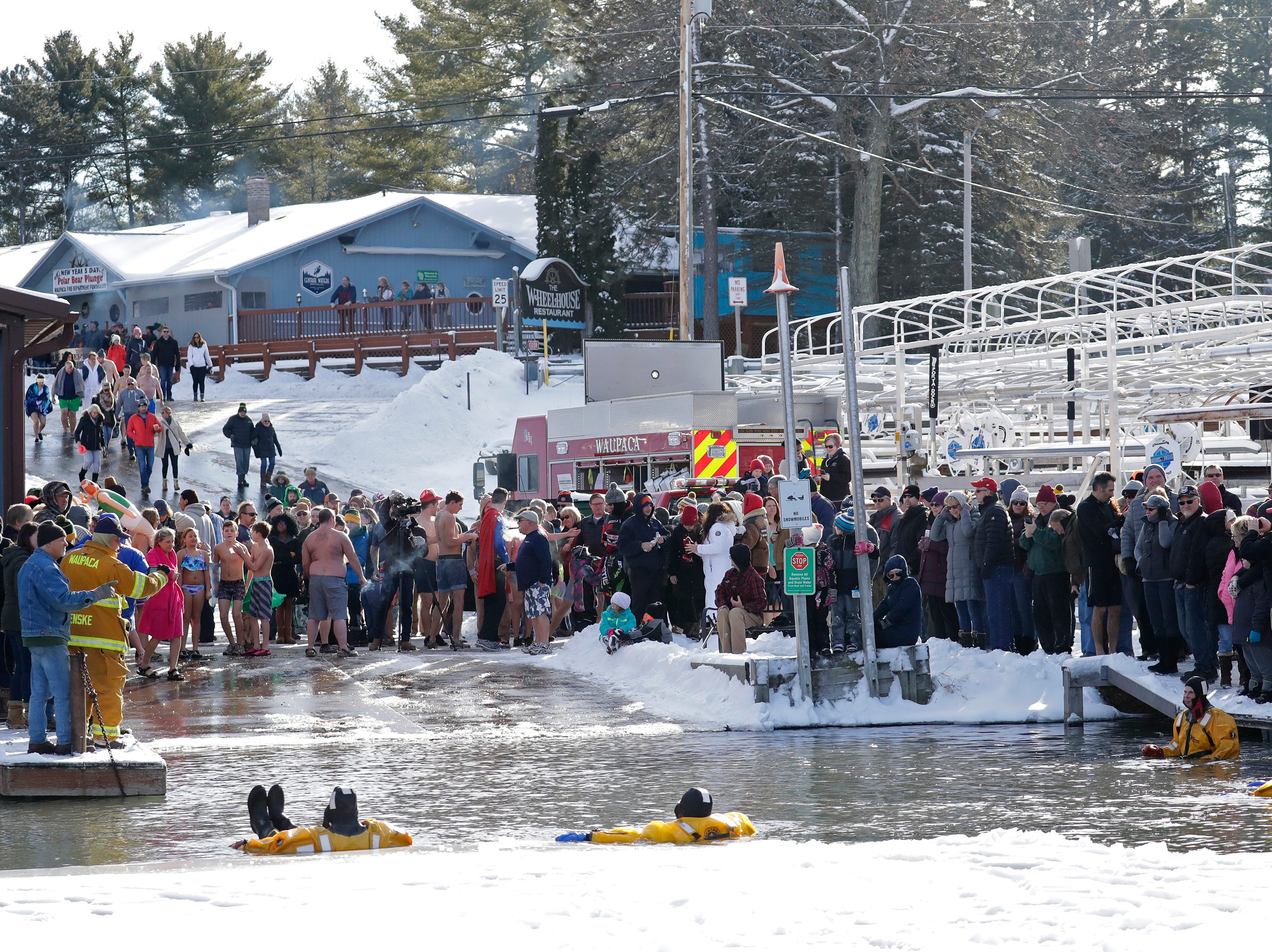 Numerous people arrive for the Polar Bear Plunge Tuesday, January 1, 2019, at Becker Marine on Lime Kiln Lake in Waupaca, Wis. 