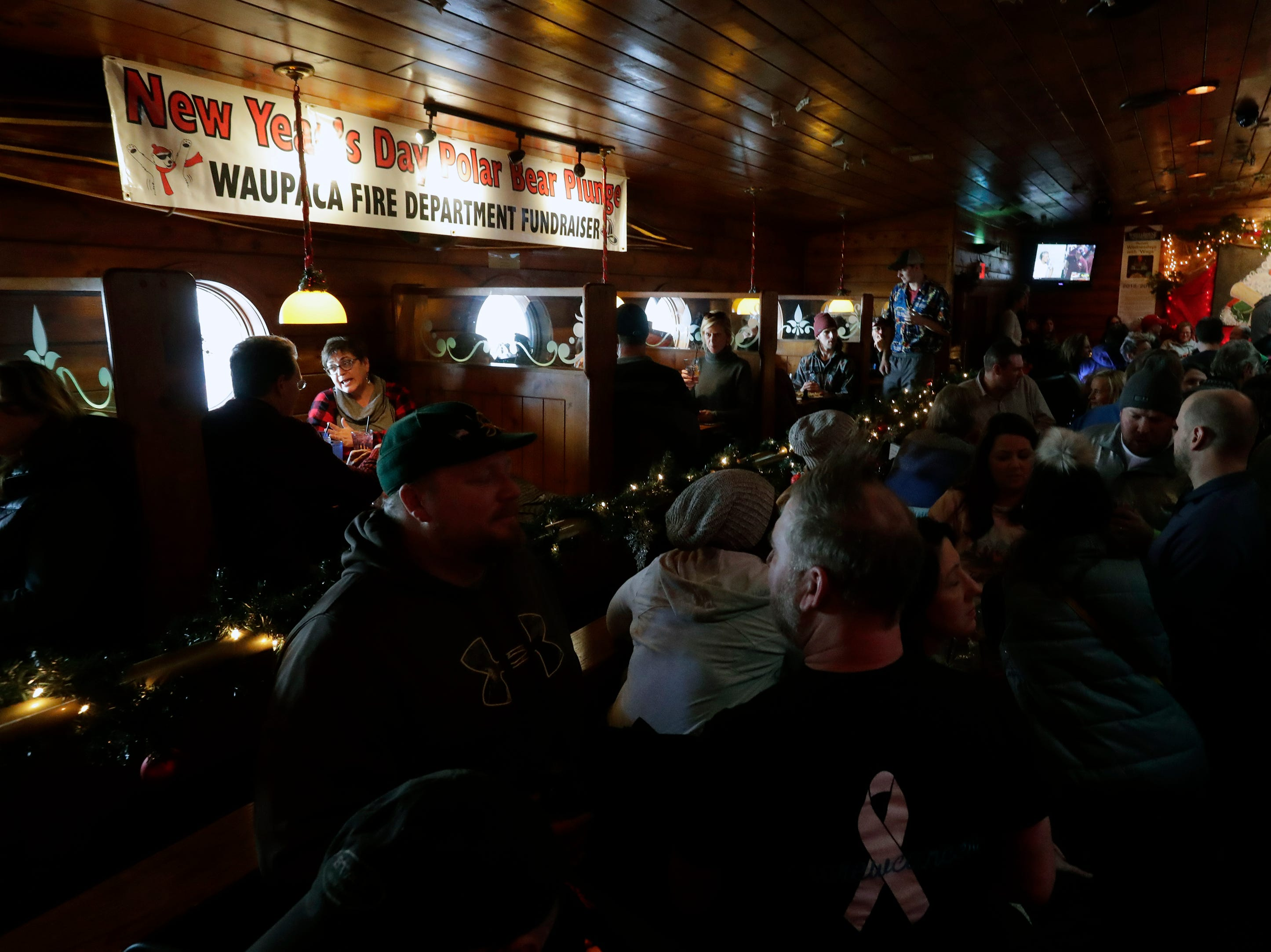 The Wheelhouse Restaurant is full of activity during the Polar Bear Plunge Tuesday, January 1, 2019, at Becker Marine on Lime Kiln Lake in Waupaca, Wis. 