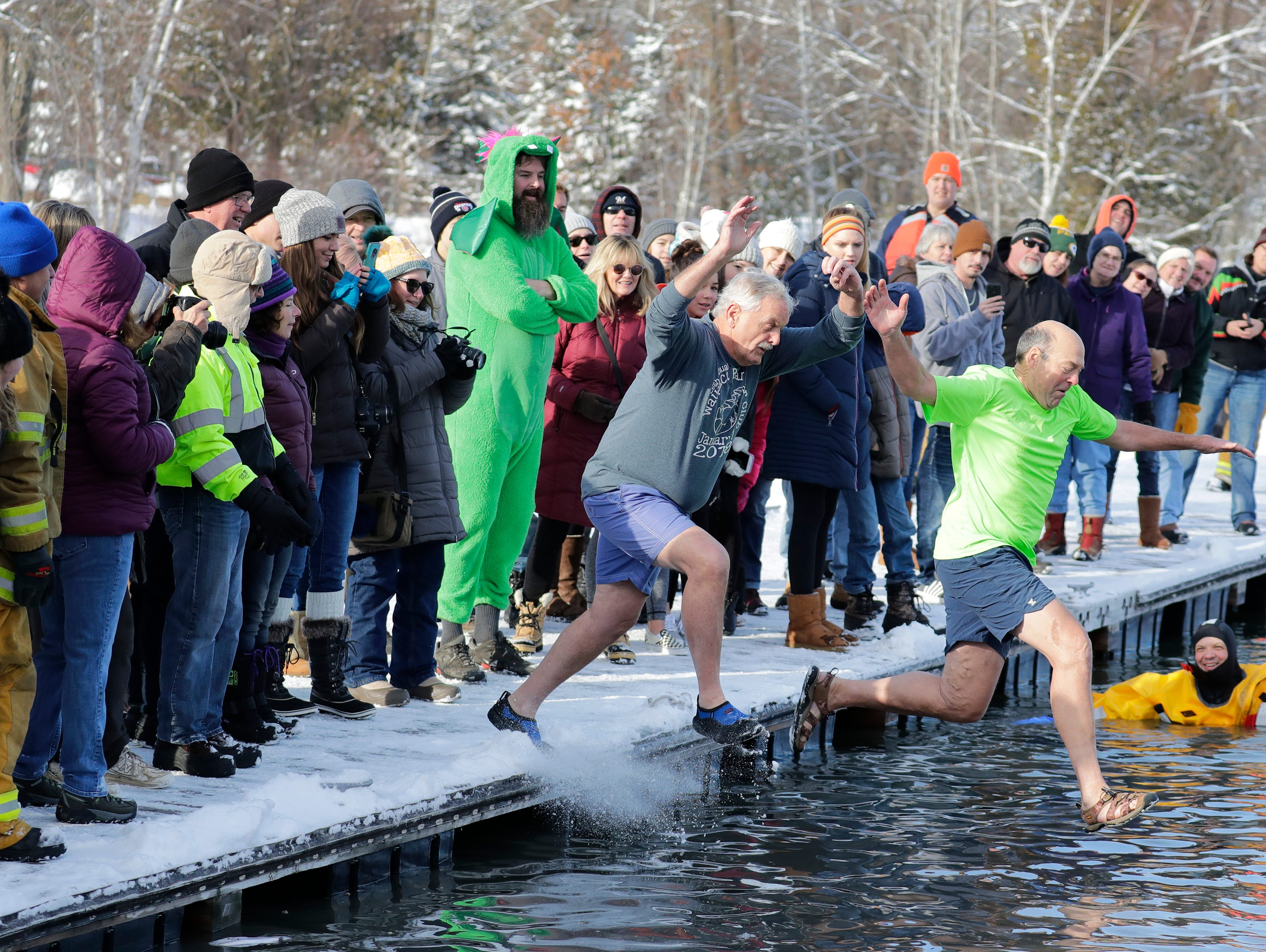 Joe Farmer, left, of Wausau and Larry Gordon of Waupaca jump into frigid waters together during the Polar Bear Plunge Tuesday, January 1, 2019, at Becker Marine on Lime Kiln Lake in Waupaca, Wis. 
