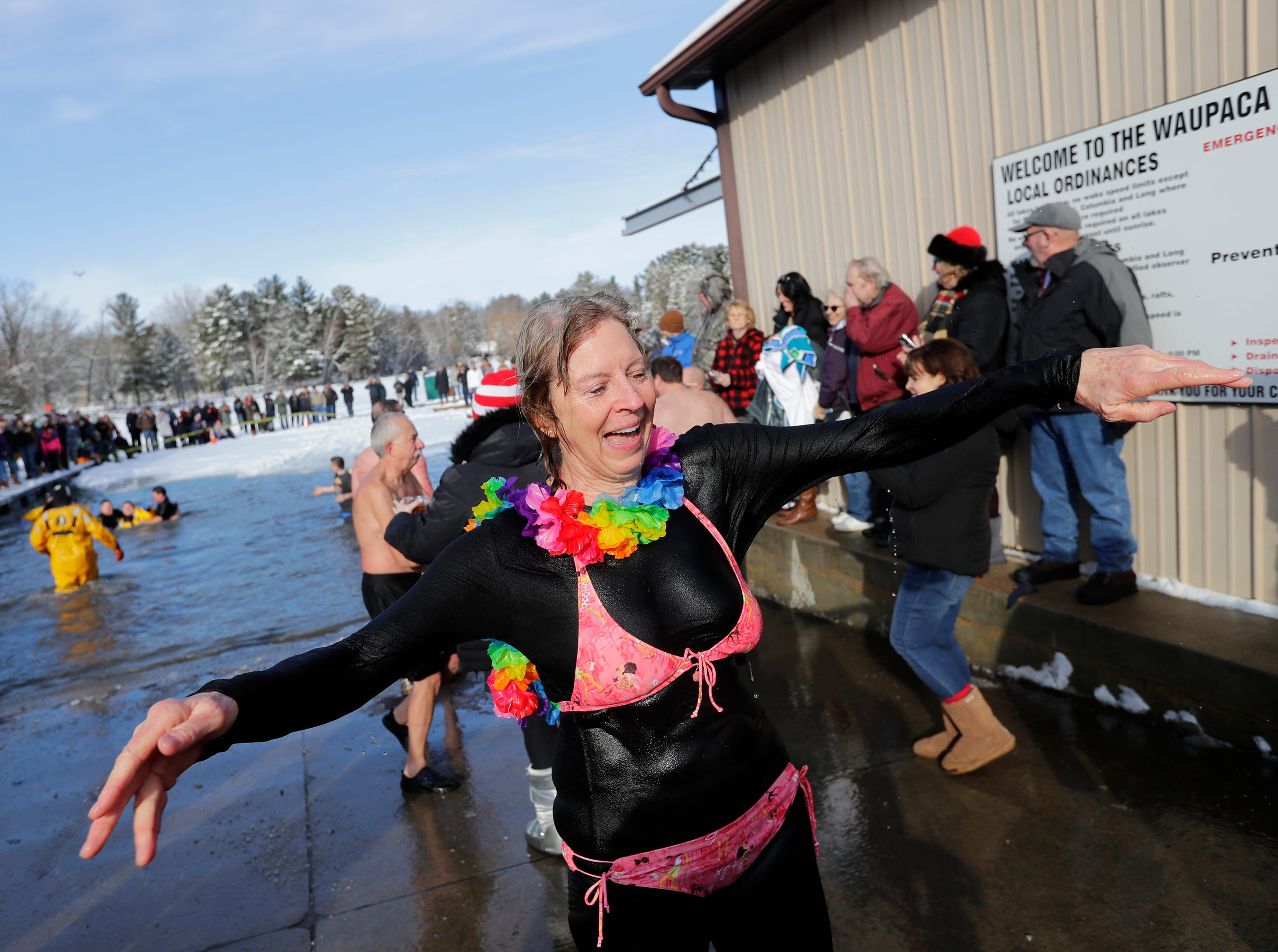 Sara Bredesen of Waupaca emerges from the bitter water during the Polar Bear Plunge Tuesday, January 1, 2019, at Becker Marine on Lime Kiln Lake in Waupaca, Wis. 