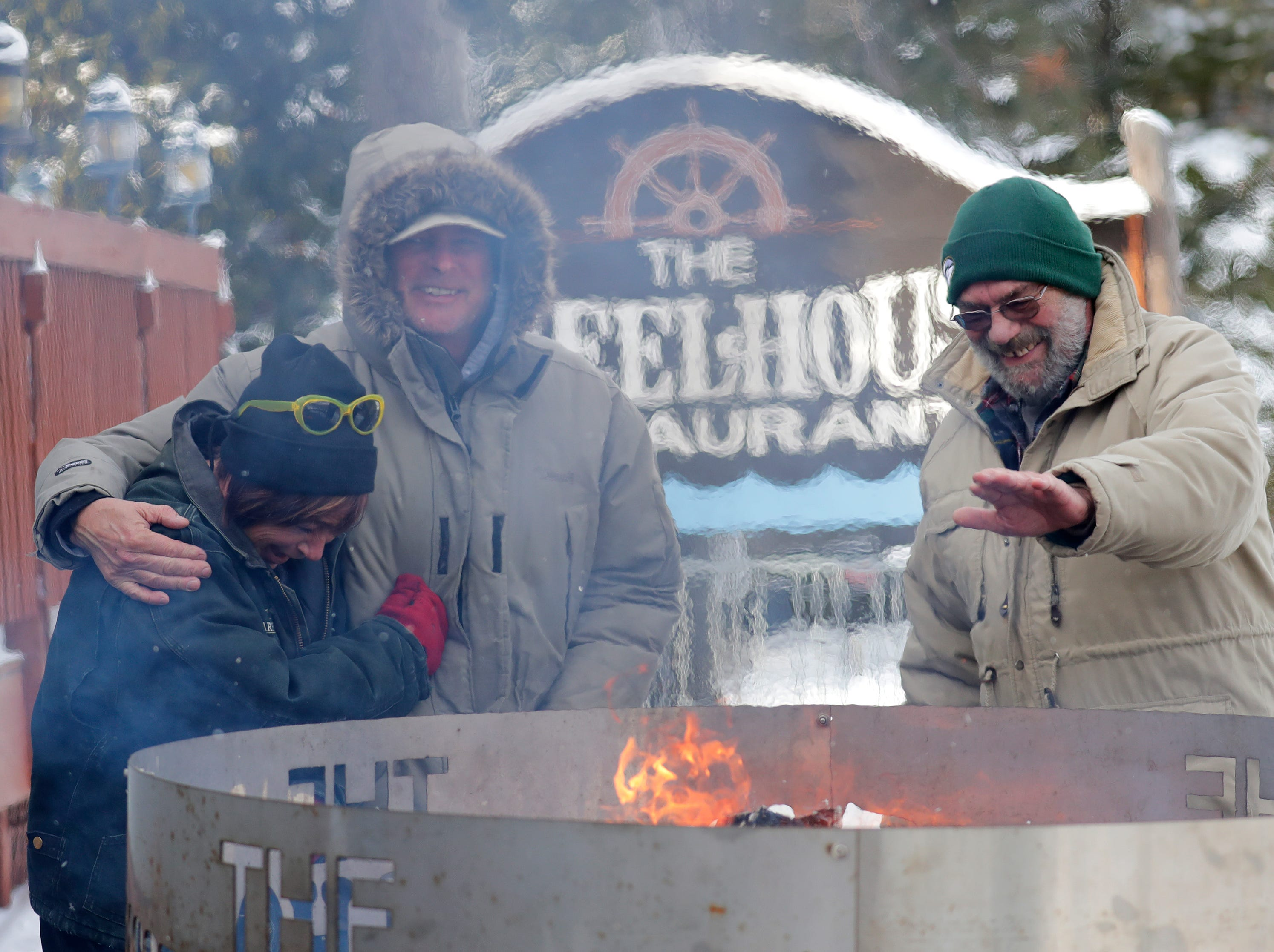 Tammy Hoeft, left, Bob Faulks and Walter Moore, right, try to stay warm outside of The Wheelhouse Restaurant during the Polar Bear Plunge Tuesday, January 1, 2019, at Becker Marine on Lime Kiln Lake in Waupaca, Wis. All three are from Waupaca.
