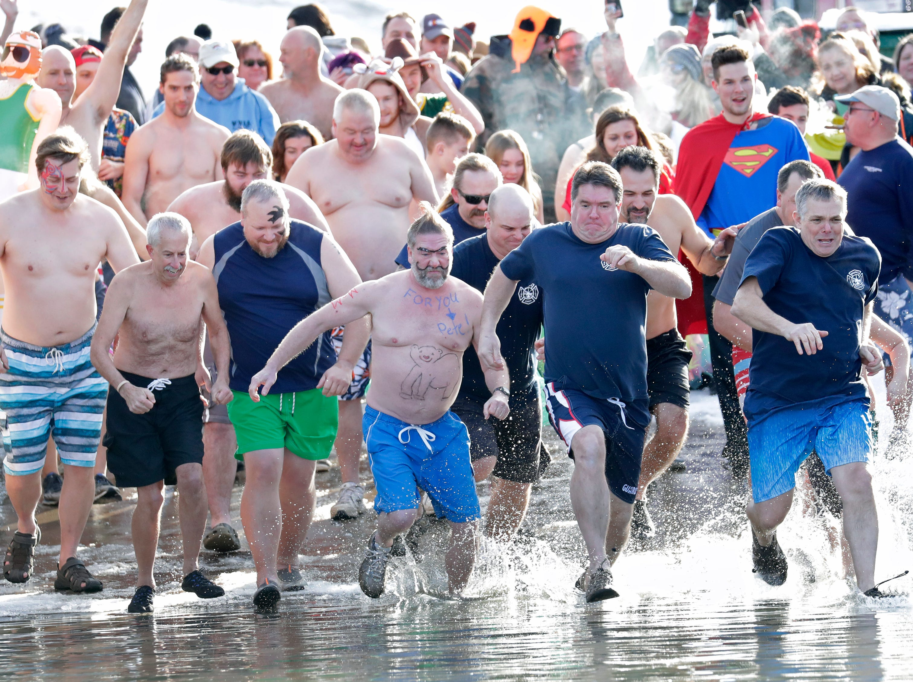 Particpants rush the bitter water at the start of the Polar Bear Plunge Tuesday, January 1, 2019, at Becker Marine on Lime Kiln Lake in Waupaca, Wis. 