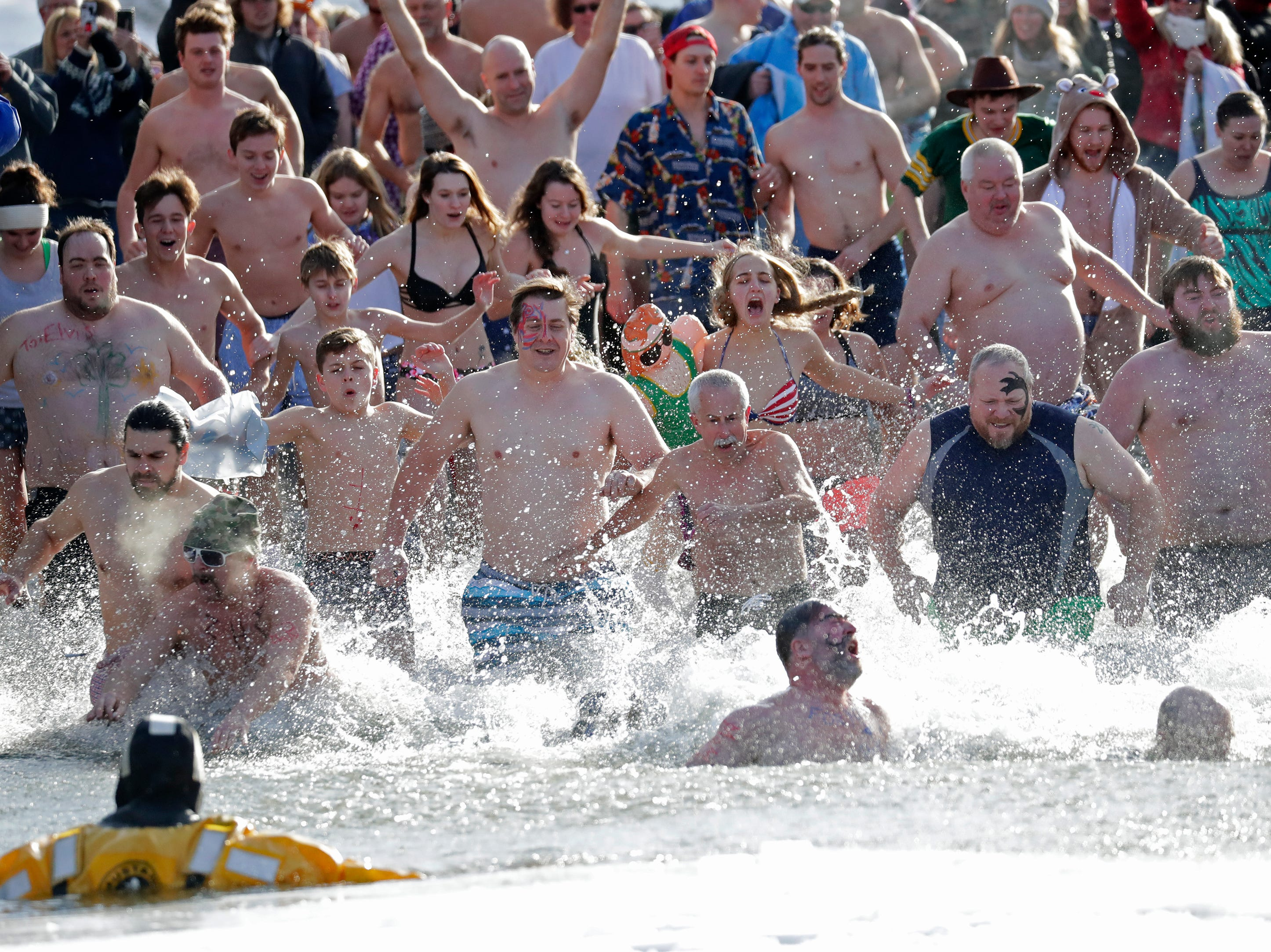 People rush into bitterly cold water during the Polar Bear Plunge Tuesday, January 1, 2019, at Becker Marine on Lime Kiln Lake in Waupaca, Wis. 