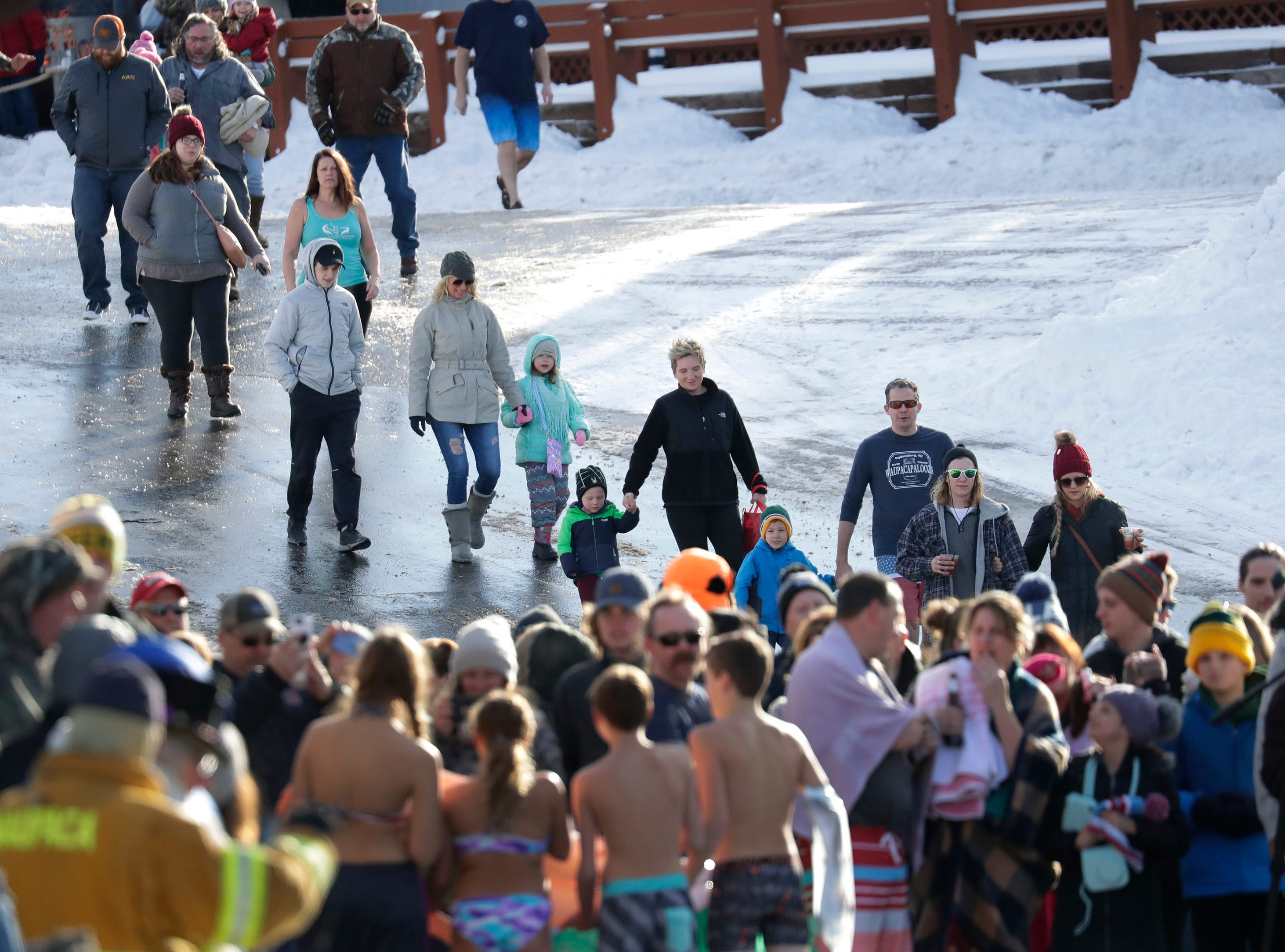 Hundreds of people arrive for the start of the Polar Bear Plunge Tuesday, January 1, 2019, at Becker Marine on Lime Kiln Lake in Waupaca, Wis. Dan Powers/USA TODAY NETWORK-Wisconsin