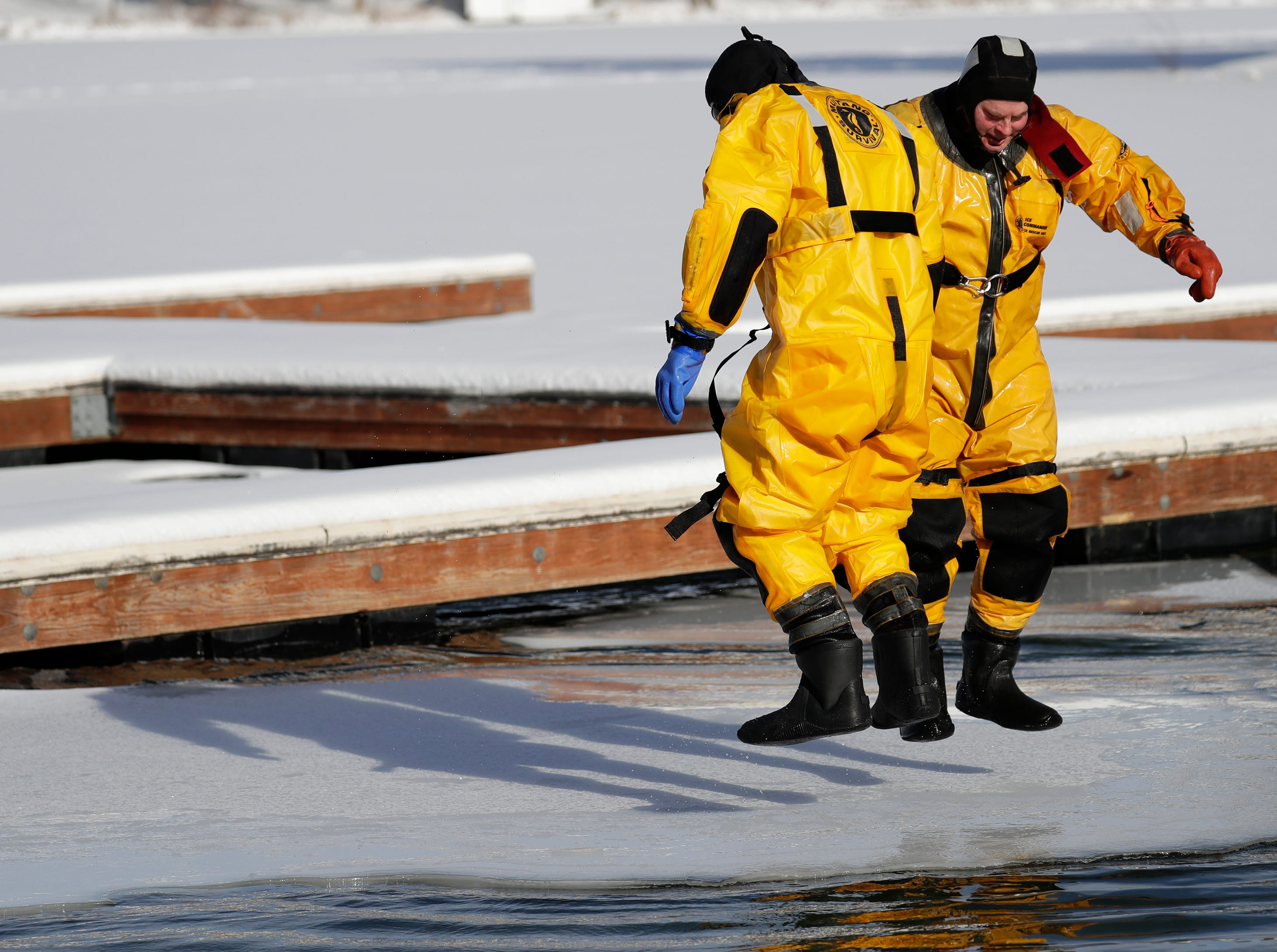 Waupaca firefighter Scott Obremski, left, and Lt. Pete Jungers jump up and down trying to break off the edge of the ice during the Polar Bear Plunge Tuesday, January 1, 2019, at Becker Marine on Lime Kiln Lake in Waupaca, Wis. 