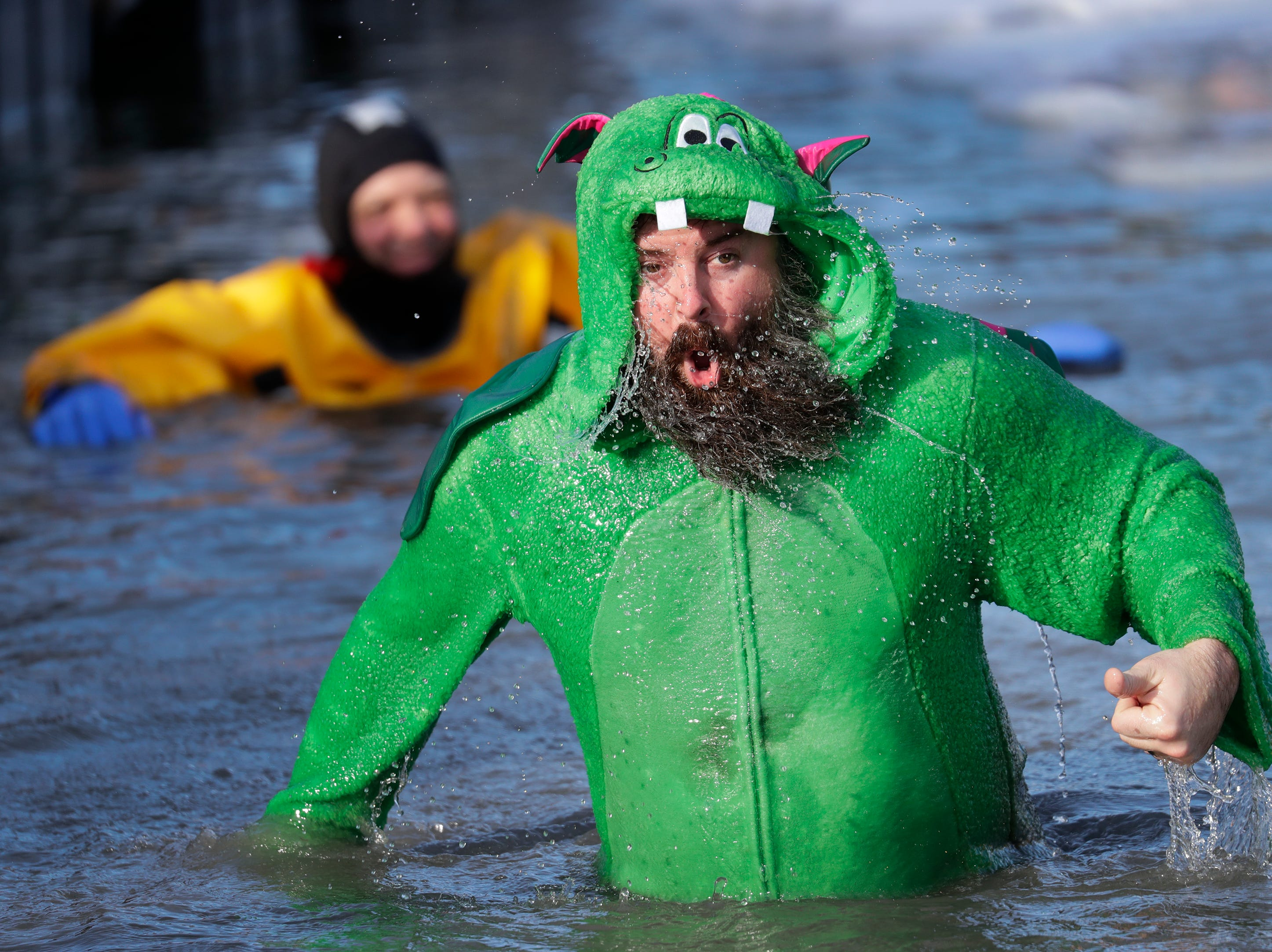 Danny Fili of Waupaca emerges from the frigid water during the Polar Bear Plunge Tuesday, January 1, 2019, at Becker Marine on Lime Kiln Lake in Waupaca, Wis. 